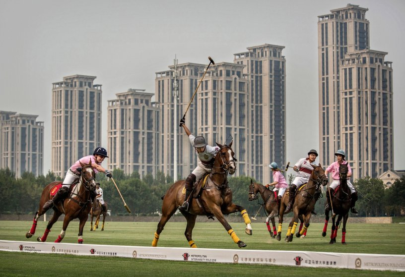 Chinese players from the Metropolitan Polo Club team, in white, and players from the U.S. and Great Britain play an exhibition match at the Tianjin Goldin Metropolitan Polo Club in Tianjin, China, on July 17, 2016.