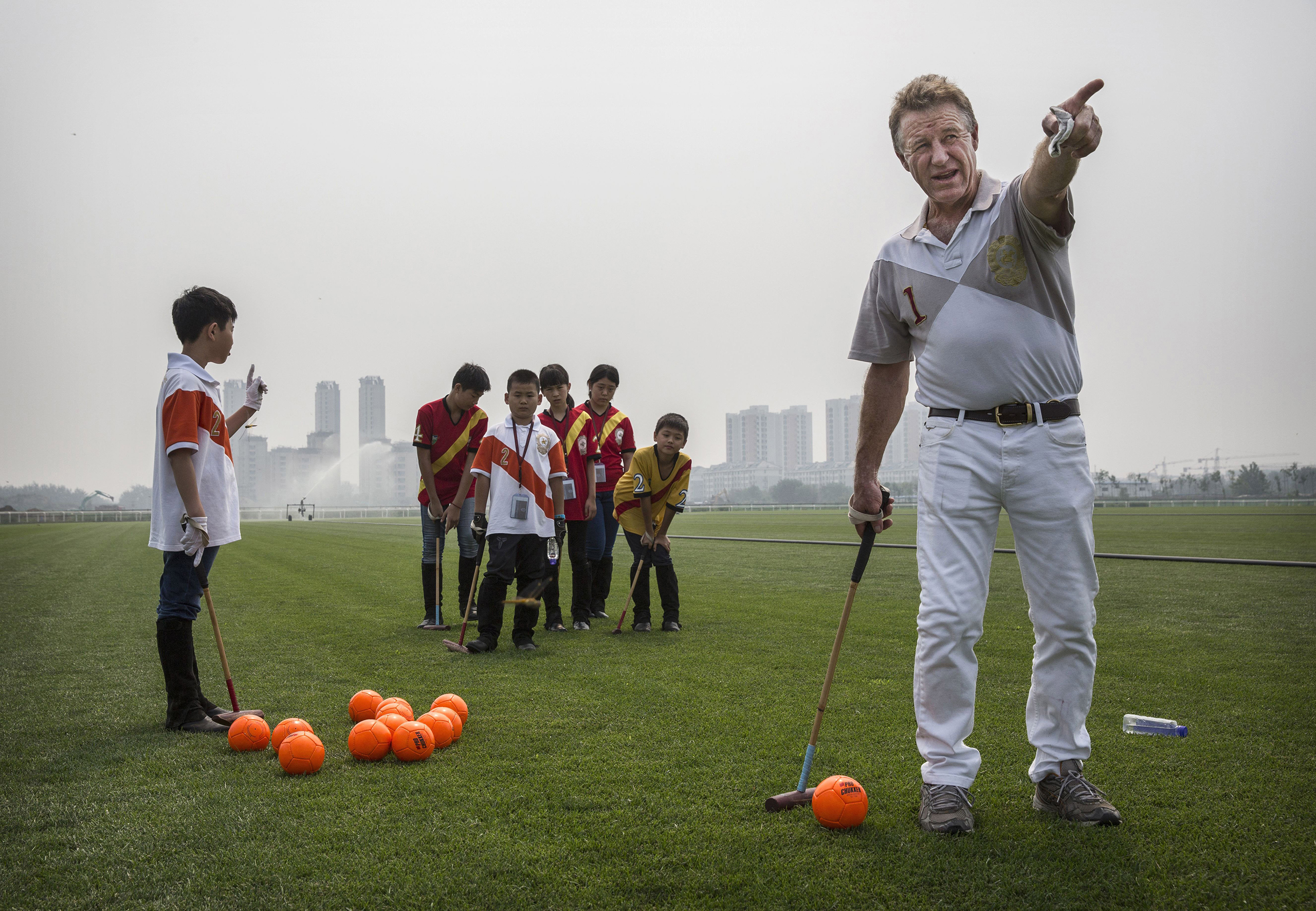 Derek Reid, director of Polo Operations, gestures as he instructs young Chinese players from the Junior Polo Program during stick and ball training at a summer camp held at the Tianjin Goldin Metropolitan Polo Club in Tianjin, China, on July 17, 2016.
