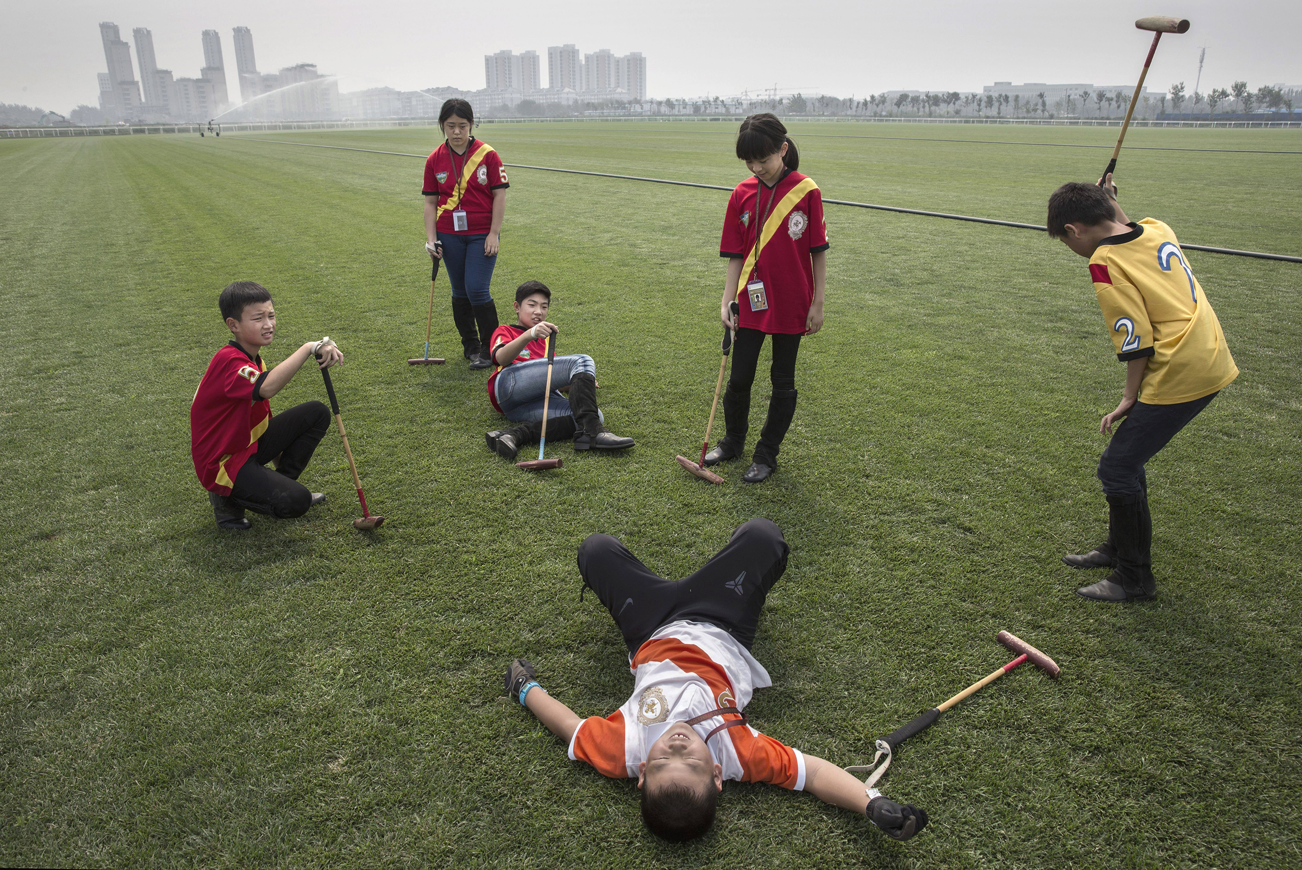 Young Chinese players from the Junior Polo Program take a break during stick and ball training at a summer camp held at the Tianjin Goldin Metropolitan Polo Club in Tianjin, China, on July 17, 2016.