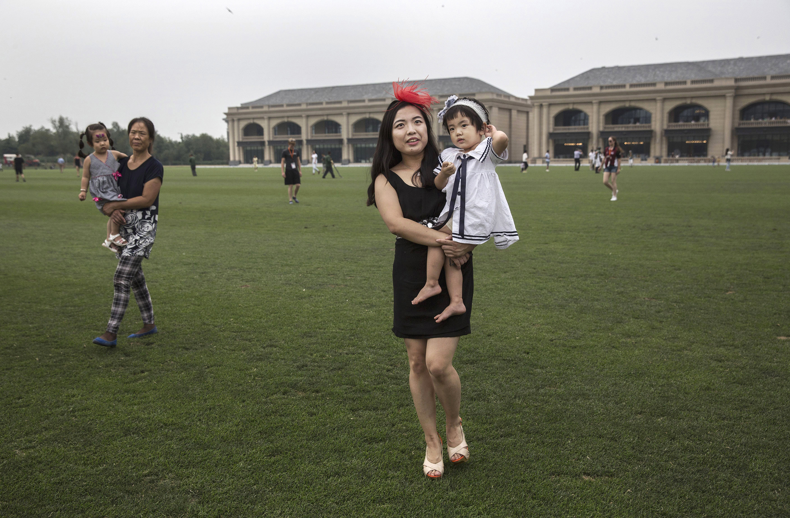 A woman walks across the field with her children during a break in an intervarsity match at the Tianjin Goldin Metropolitan Polo Club in Tianjin, China, on July 16, 2016.