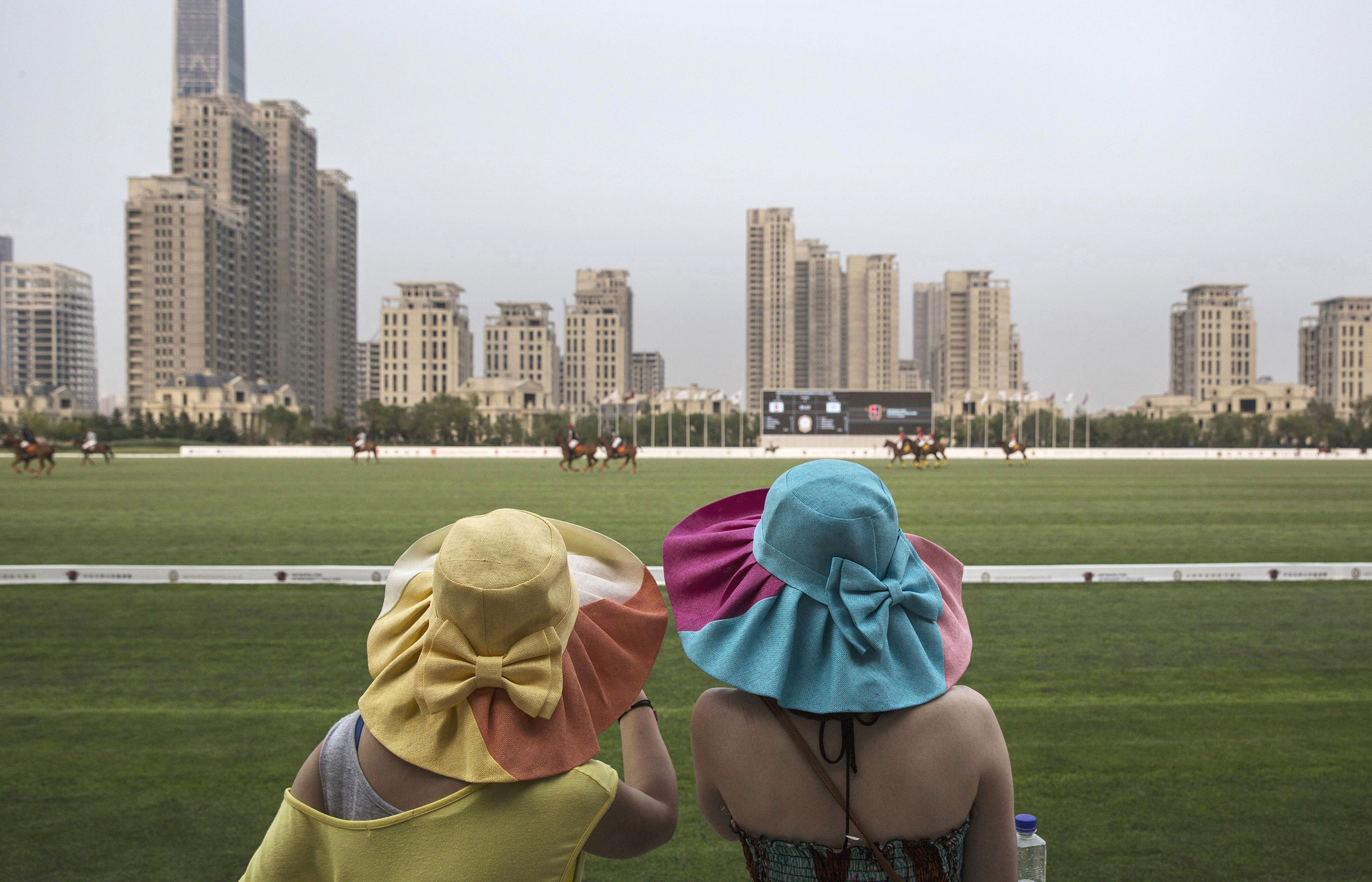 Spectators watch a match between Chinese players from the Metropolitan Polo Club team and those visiting from the U.S. and Britain during the intervarsity tournament at the Tianjin Goldin Metropolitan Polo Club in Tianjin, China, on July 17, 2016.