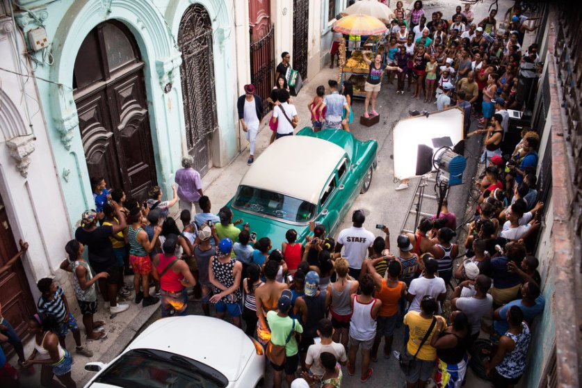 Fans crowd the set of this music video shoot in Old Havana with artists Divan and El Principe. The set includes typical elements of the neighborhood, a fruit stand and a classic American car. 9/24/2015