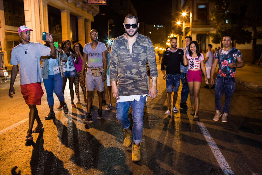 Singer El Principe from Los Desiguales is followed by fans during a late night portrait session on Havana's Galiano Street on Feb. 15, 2016. He is known for his keen fashion sense which he calls Fashatón.