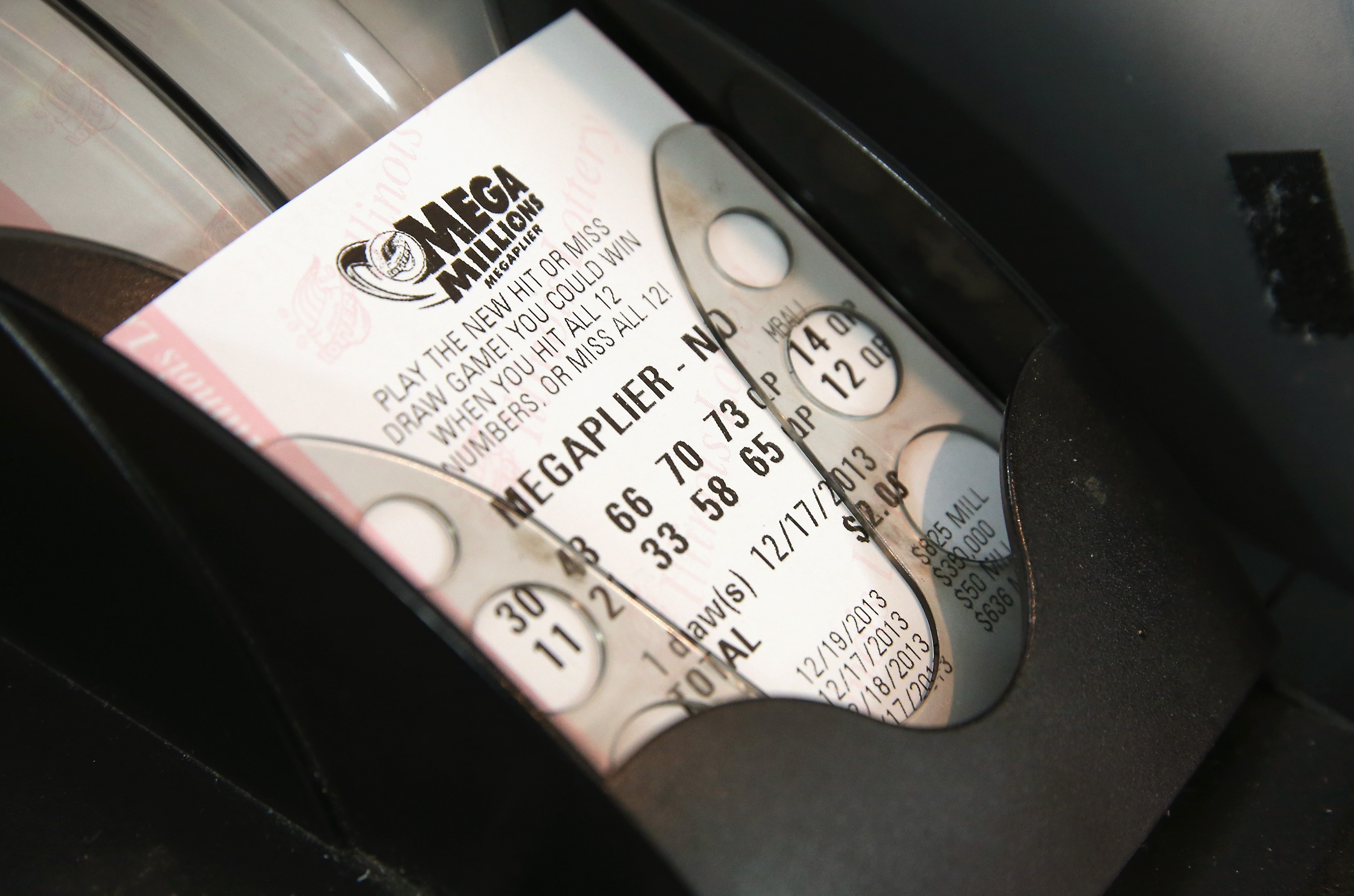 A machine prints a Mega Millions lottery ticket for a customer at a convenience store  in Chicago on Dec.17, 2013.