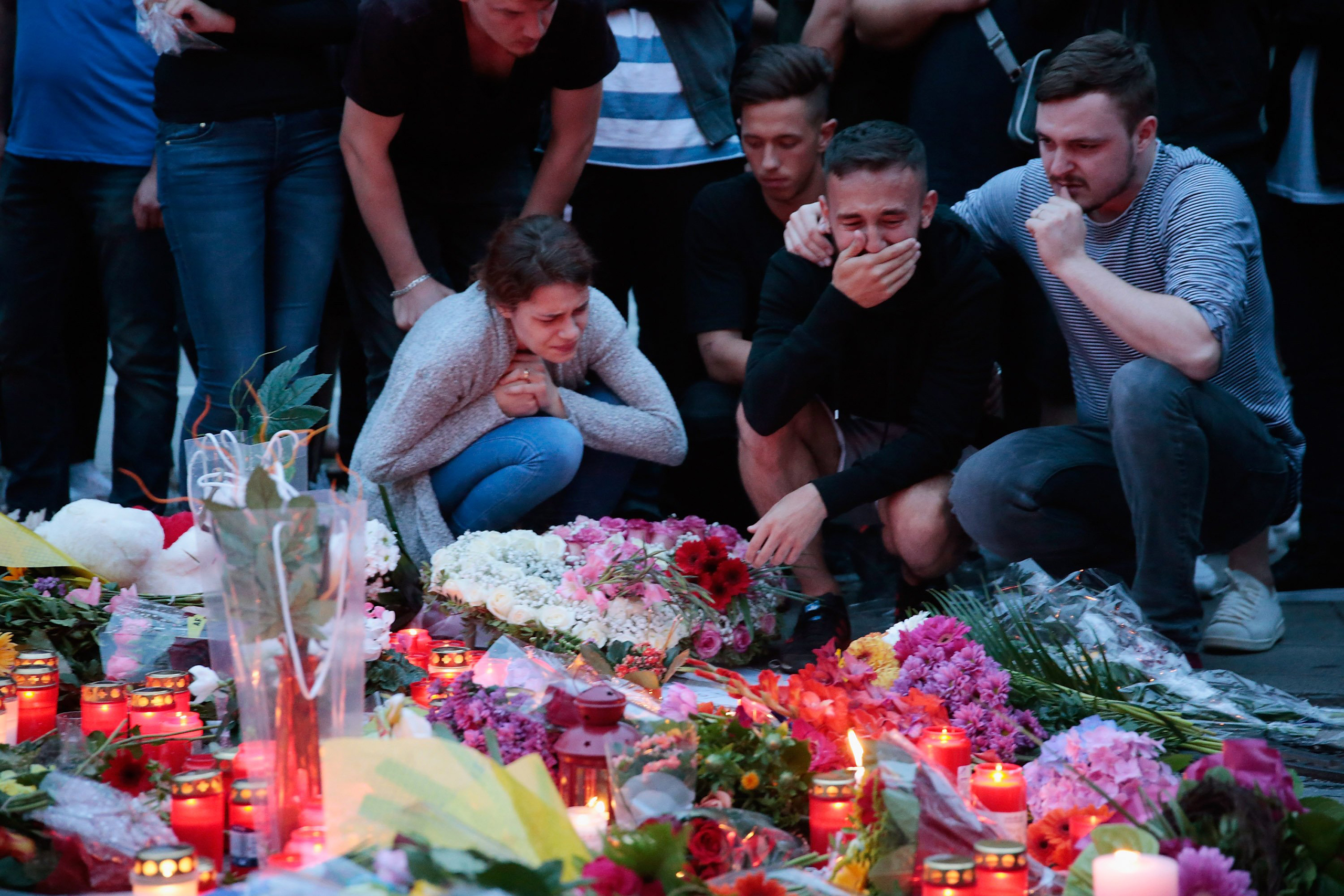 People mourn near the crime scene at OEZ shopping center the day after a shooting spree left nine victims dead in Munich, Germany, on July 23, 2016.