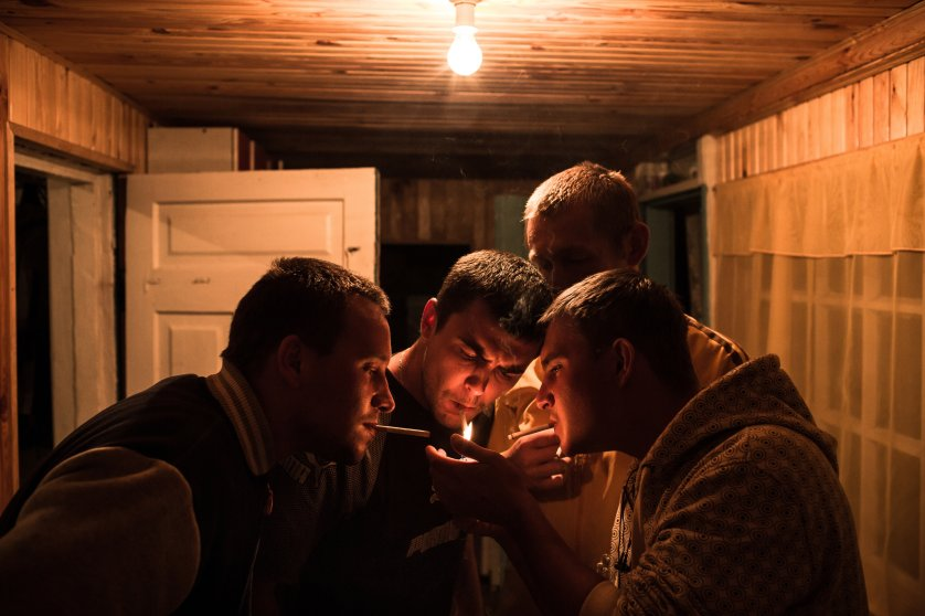 Kiril, Vladik, one of his friend and Ruslan are lighting a cigarette before going out in a village to buy some more vodka.