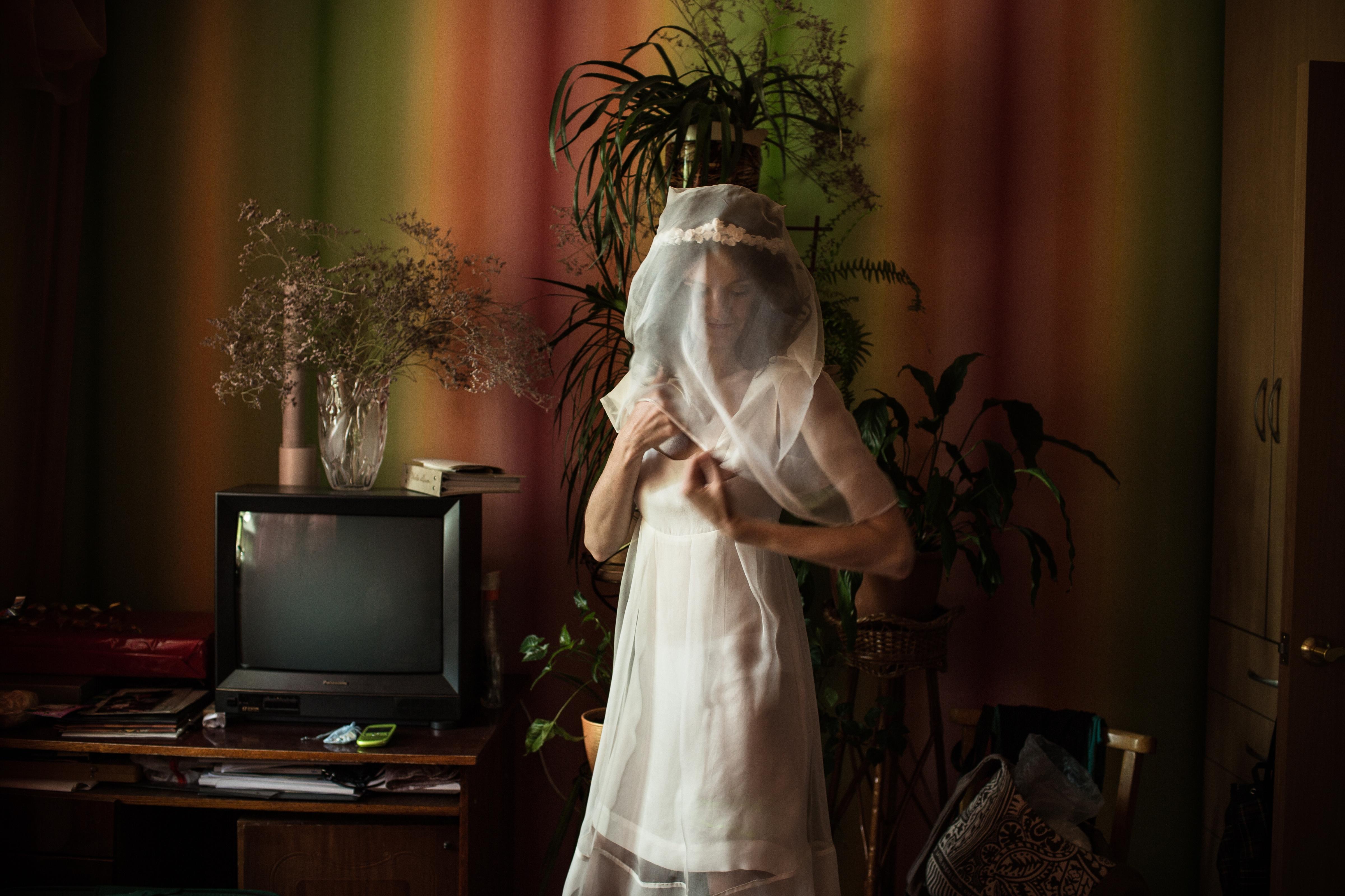 Yulia puts on her wedding dress in her room, on June 19 2013 in Slavutych, Ukraine.