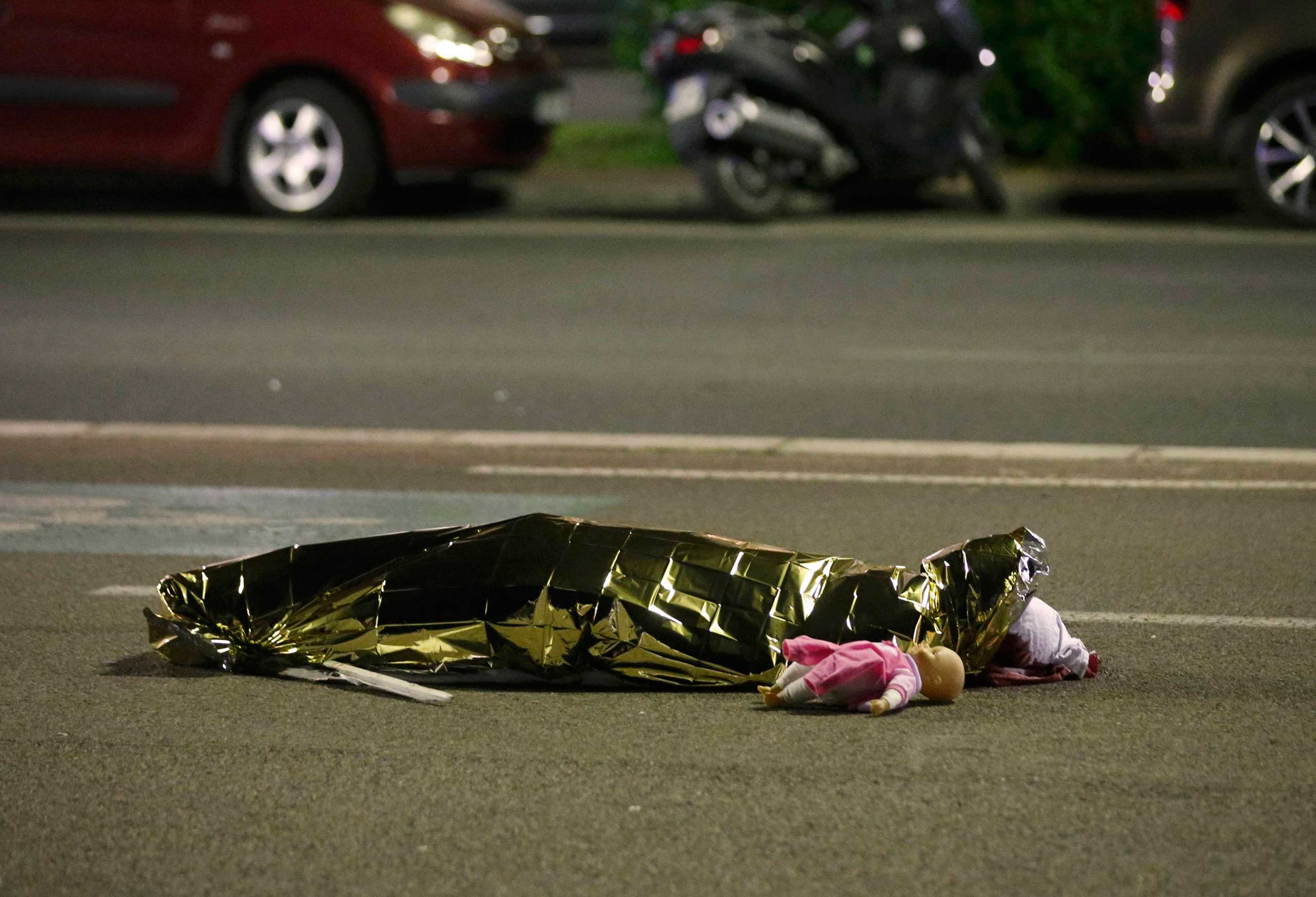 A body is seen on the ground July 15, 2016 after at least 84 people were killed in Nice, France, when a truck ran into a crowd celebrating the Bastille Day national holiday.
