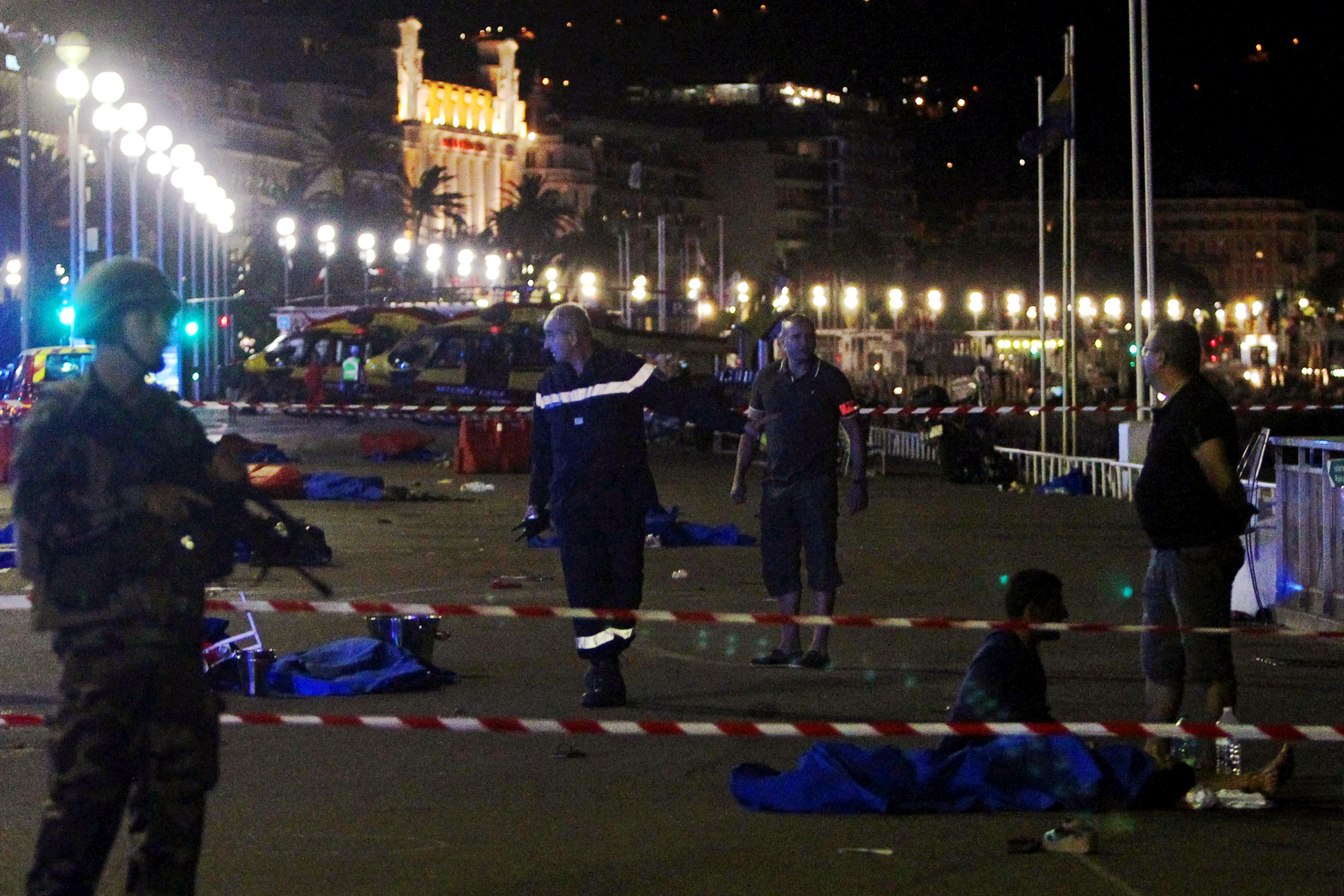 Soldiers, police officers and firefighters walk near bodies on the Promenade des Anglais seafront in the French Riviera town of Nice on July 15, 2016, after a van drove into a crowd watching a fireworks display.