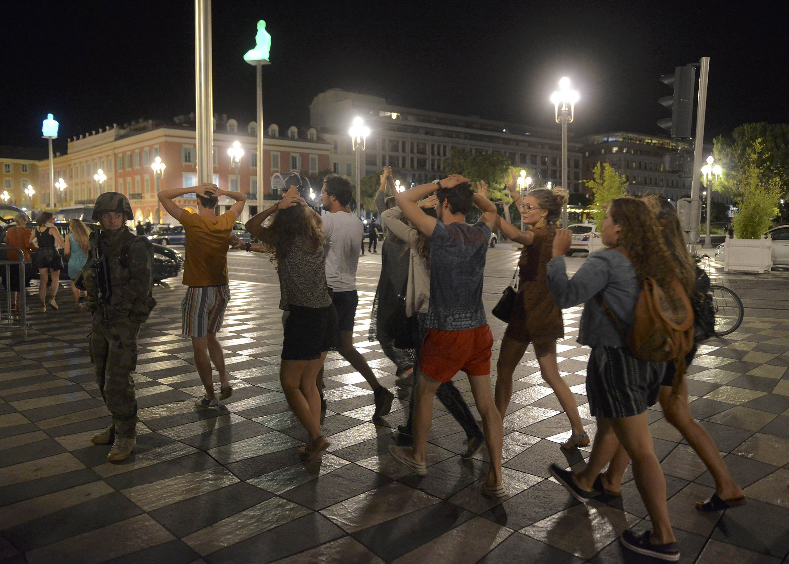 People cross the street with their hands on their heads as a French soldier secures the area in Nice, France, on July 15, 2016, after at least 60 people were killed along the Promenade des Anglais when a truck ran into a crowd celebrating Bastille Day.