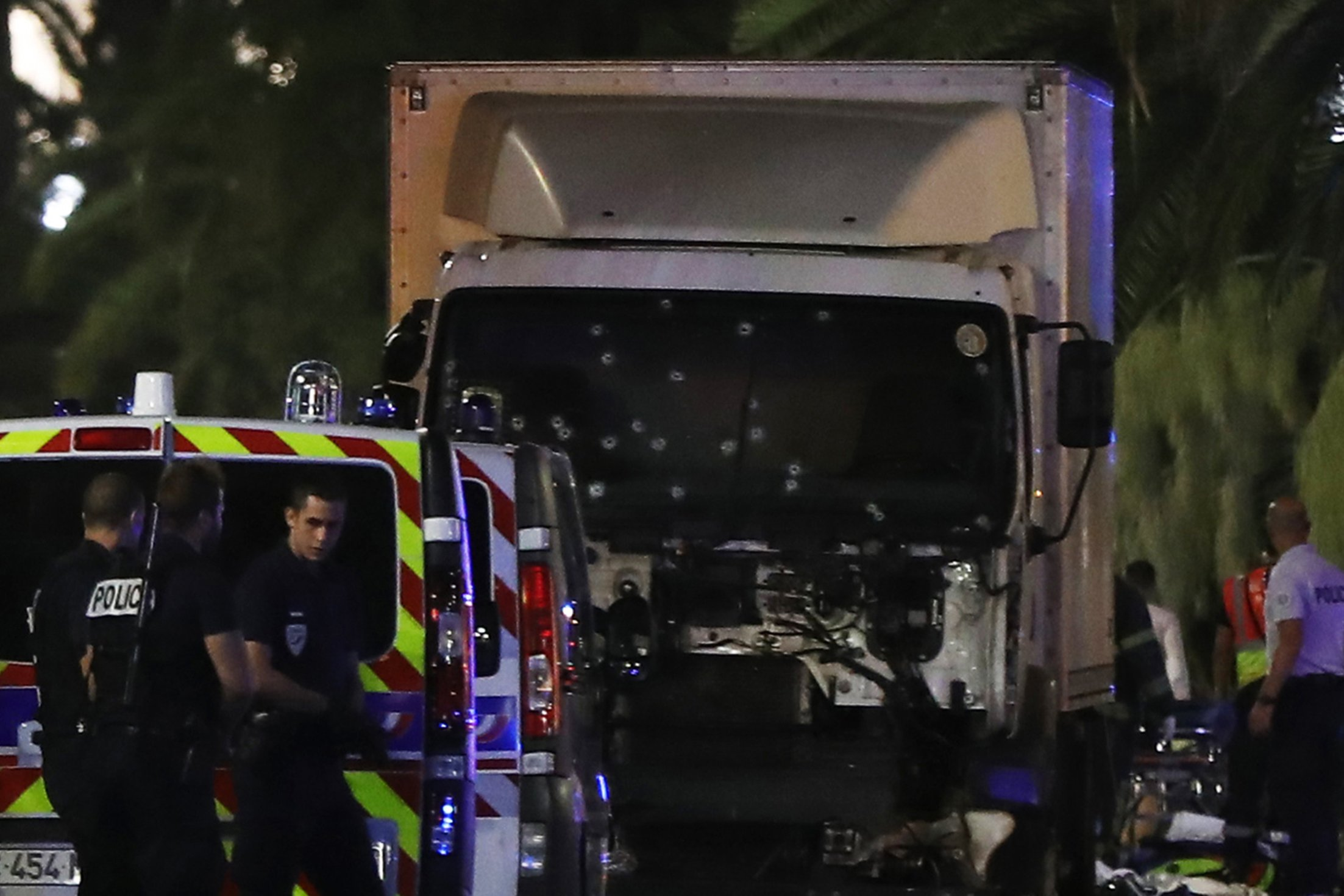 Police officers stand near a van, with its windscreen riddled with bullets, that tore into a crowd leaving a fireworks display in the French Riviera town of Nice on July 14, 2016