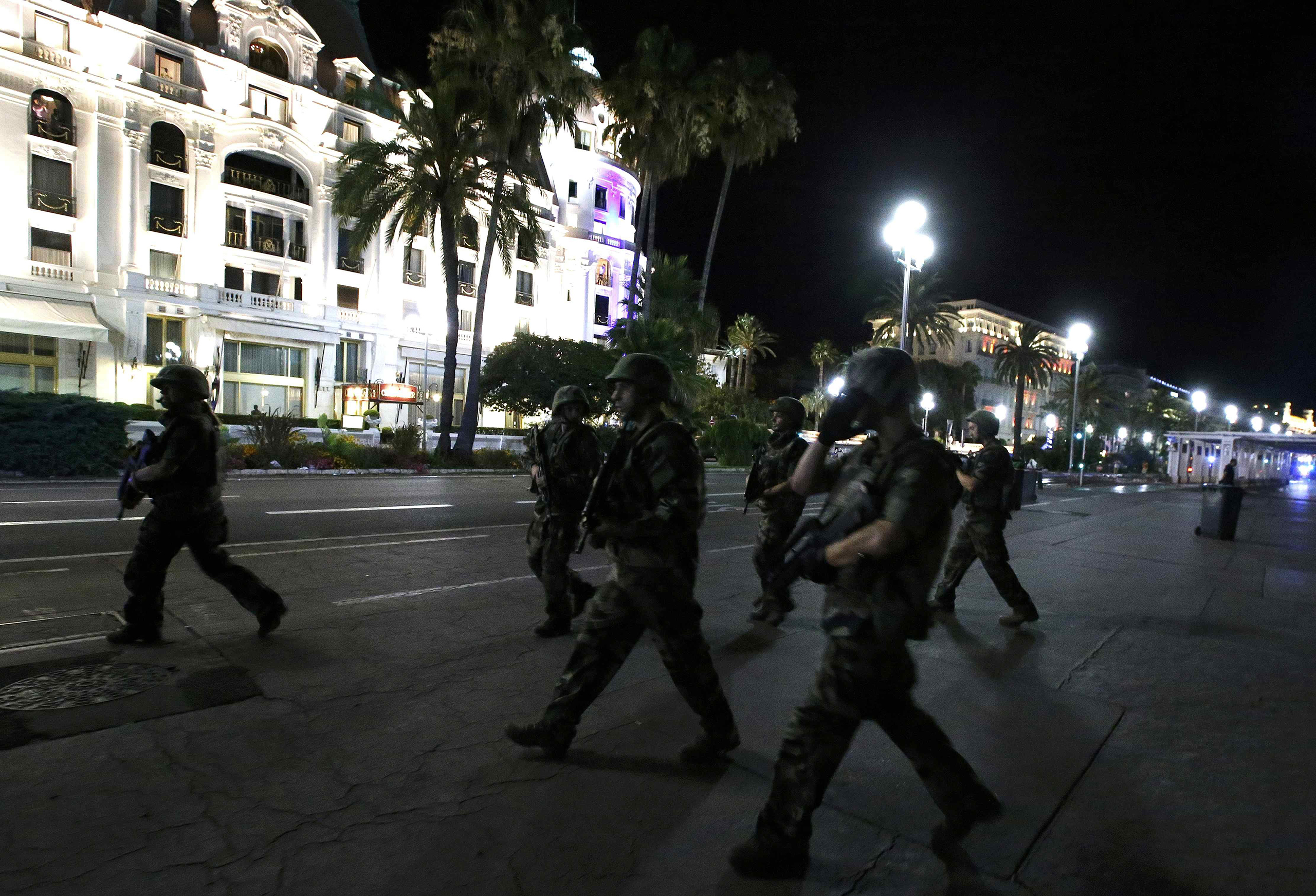 French soldiers advance on the street after at least 70 people were killed in Nice, France, when a truck ran into a crowd celebrating the Bastille Day national holiday on July 14, 2016.