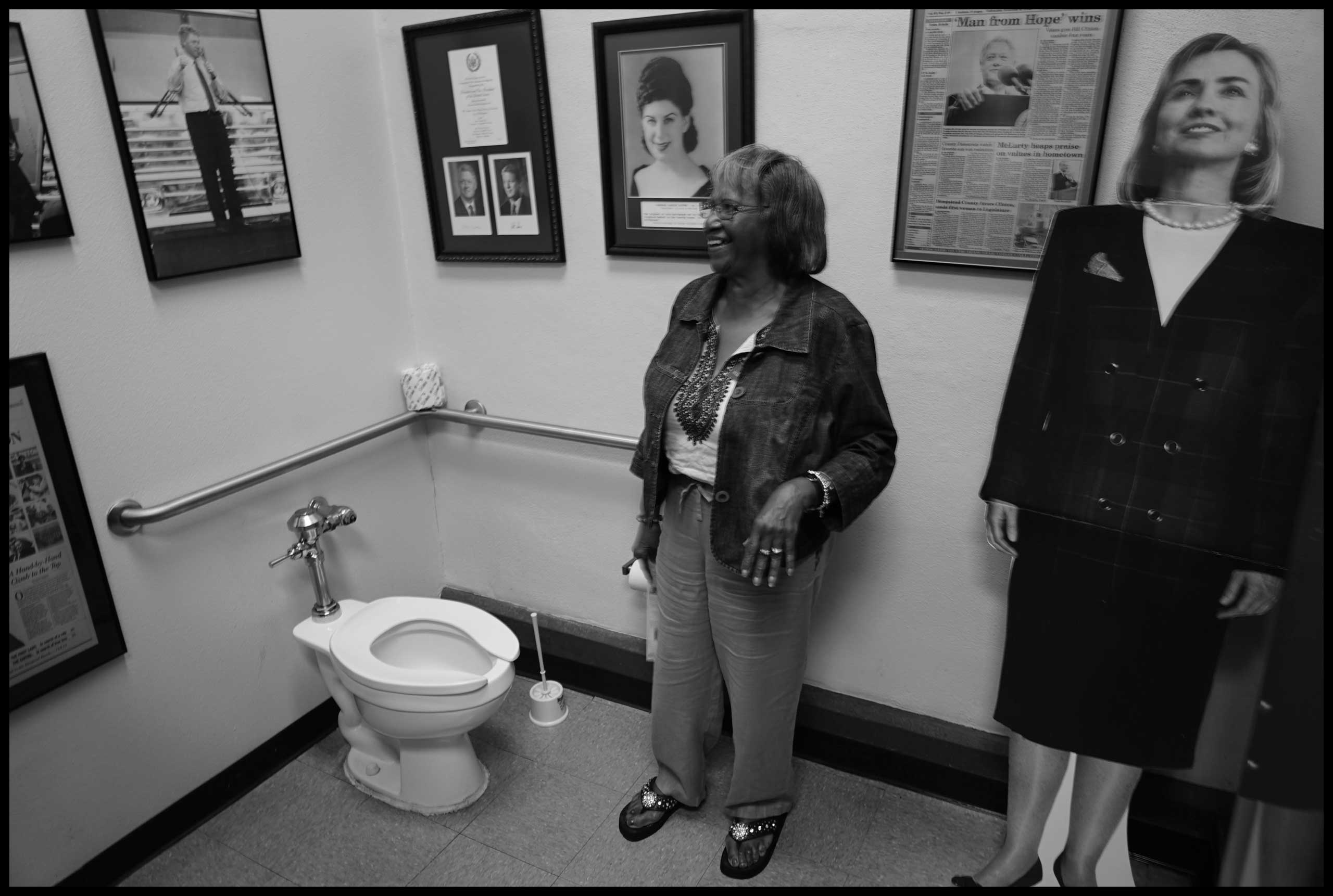 Margaret Smith inside female rest room where placard of Hillary Clinton is on display. Hope, Ark. 2016.