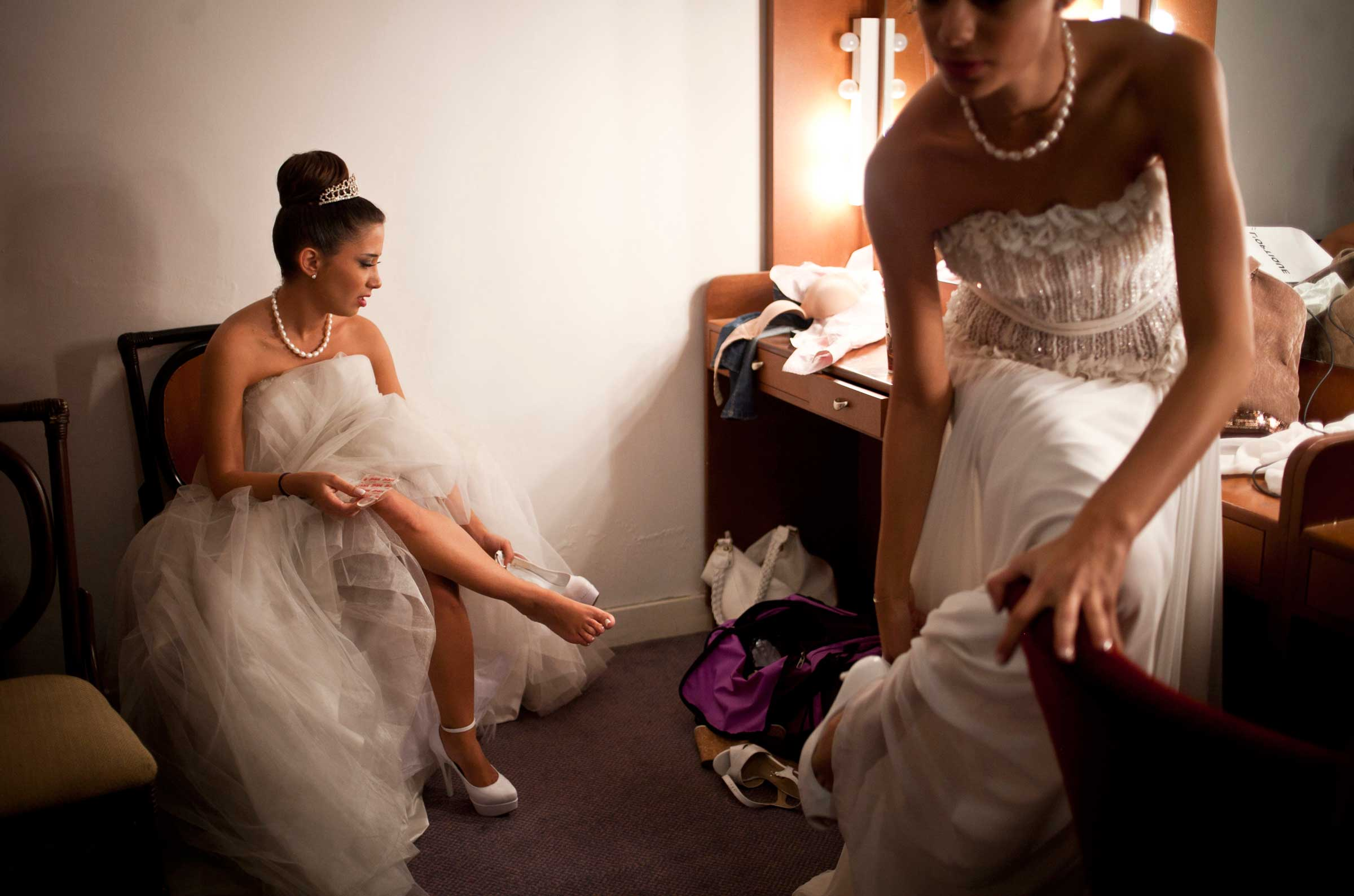 Dima Arabi, the oldest Debutante participant, 24, after her hair and make up has been applied, puts her dancing shoes on in the communal dressing room, before the Ball.