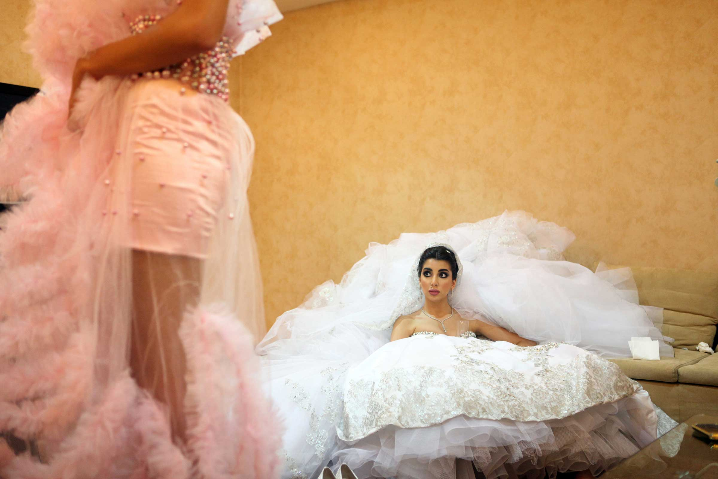 Sara, 22, who graduated five days before her wedding, waits in a holding room before she makes her entrance to her 650- guest wedding in BIEL Center, Beirut, Lebanon. Her dress weighs 15 kilos.