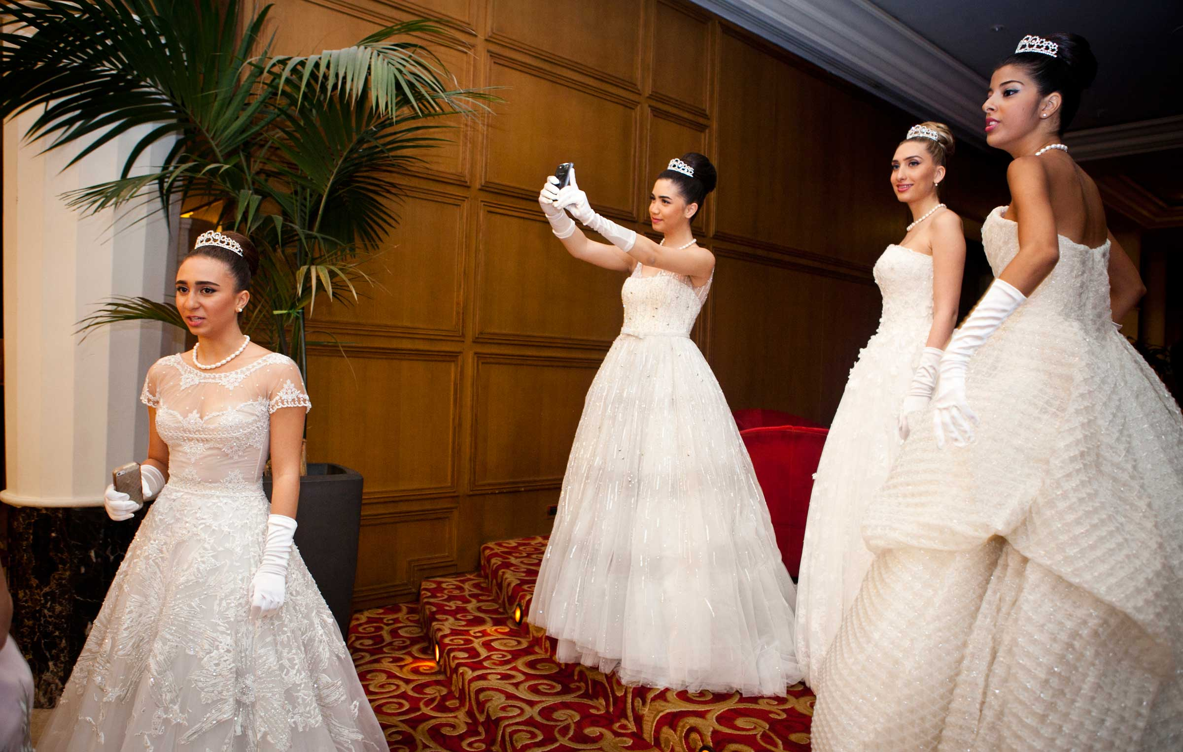 Taline Mansour, (center) poses for a self portait on her mobile phone, while amongst Debutante Ball participants, before the Ball at Casino du Liban where the Ball is held.