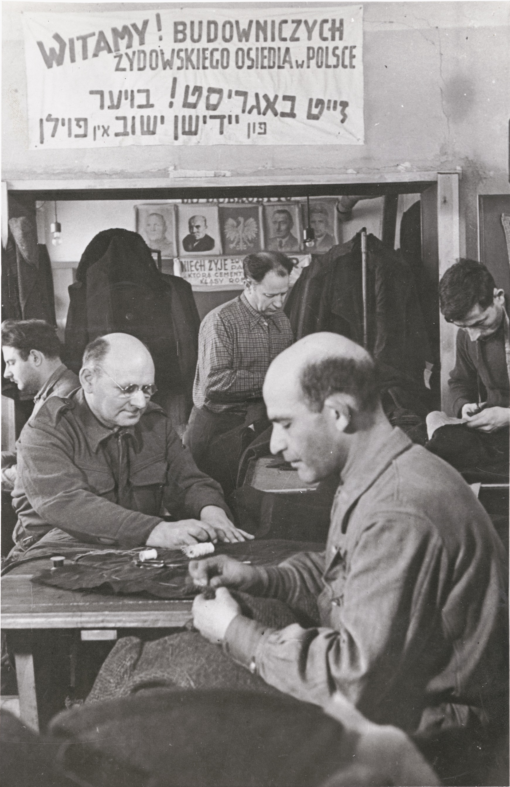 """Polish Jews, among them repatriates, work in a tailor shop with a sign that reads in Polish and Yiddish, """"Welcome! Building of the Jewish Community in Poland,"""" Dzieroniow, 1946. After World War II, Dzieroniow, in Lower Silesia, became a major Jewish resettlement center. Survivors went there to begin new lives."""