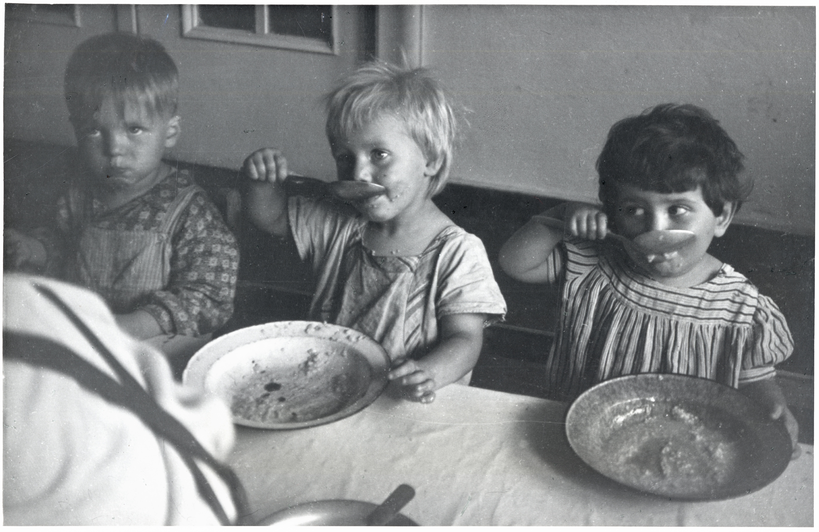 Children eating lunch at a day care center in Sczeczyn; the centers were designed to care for children whose mothers had to work. Sczeczyn, Poland, 1948.
