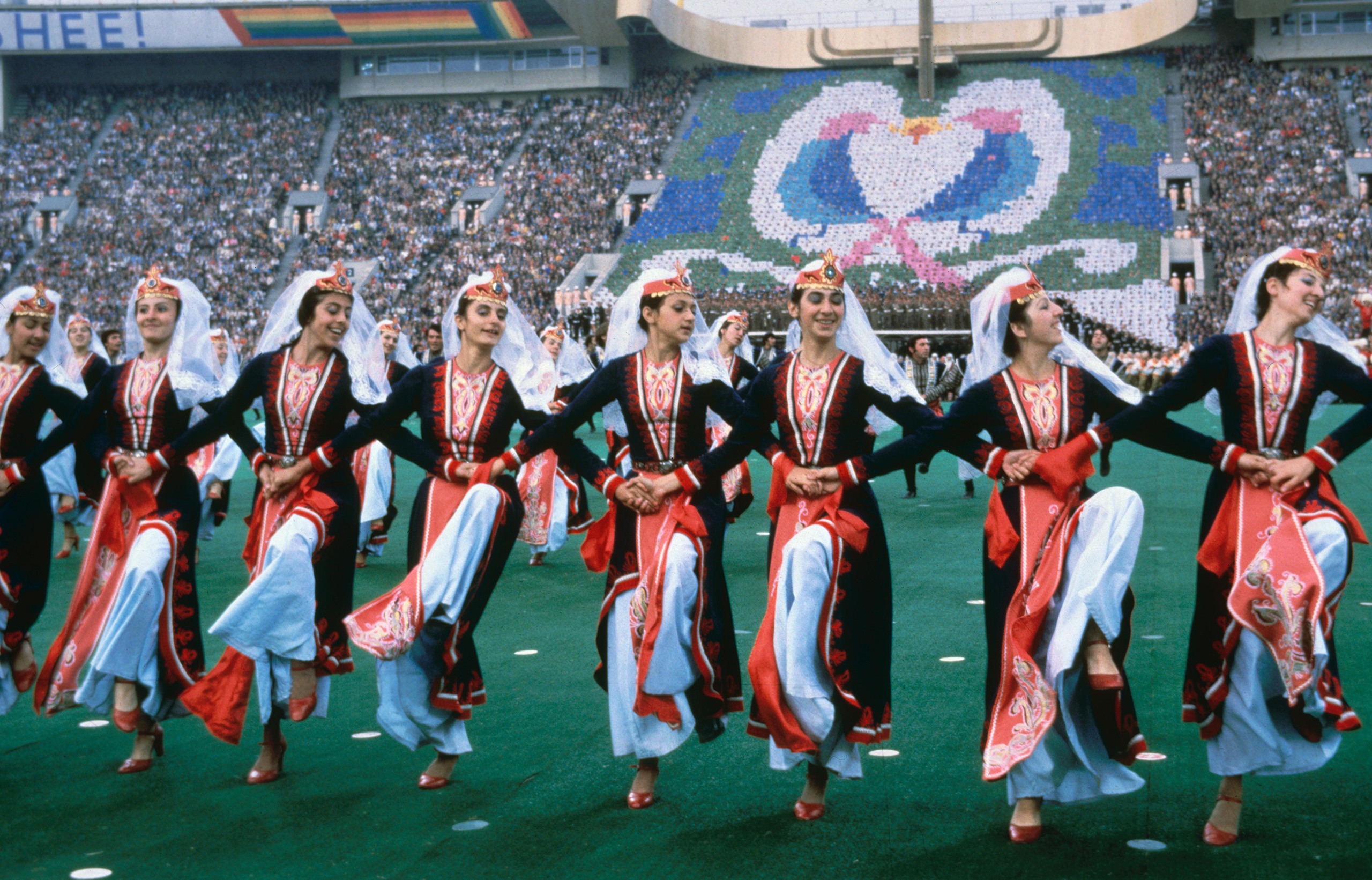 Moscow, 1980Russian dancers perform a folkloric dance with a human mosaic depicting birds in the background.