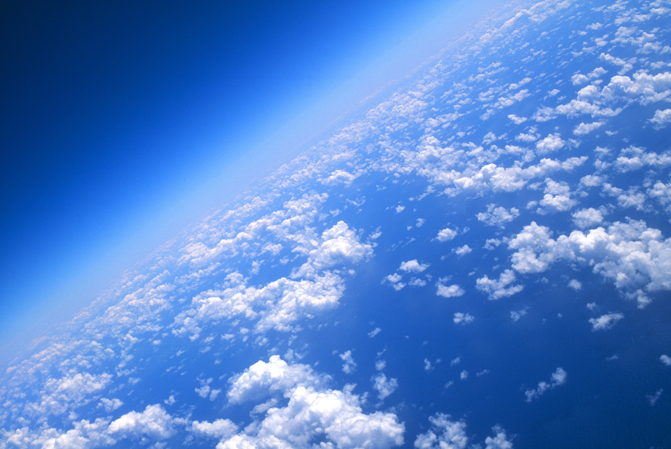 View of world from 40000 feet, clouds and blue sea.