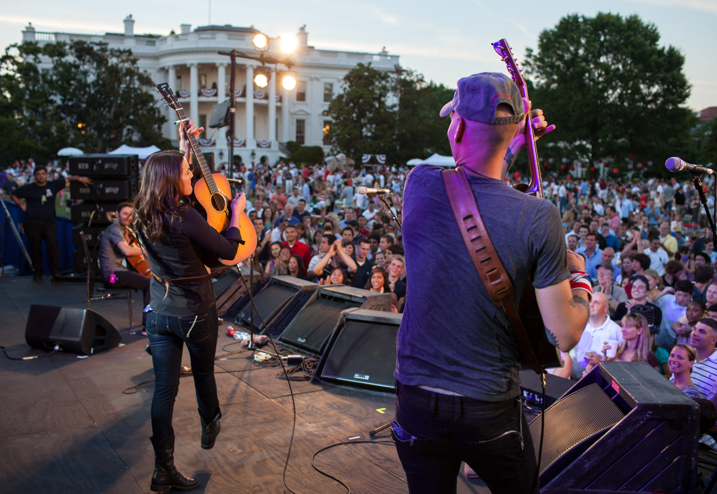 """July 4, 2010                               Pete Souza: """"Every year, we have a different band, or sometimes two bands, perform for military families and White House staff. It's actually the United Service Organizations that sponsors it. Even though it's on our turf, the USO and most bands never wanted me to be on the stage. But this year, I happened to know Brandi Carlile and her manager, so asked them if I could be onstage during their performance to line up the White House in the background.""""                               President Barack Obama and First Lady Michelle Obama host a Fourth of July celebration with military personnel and their families on the South Lawn of the White House, July 4, 2010."""