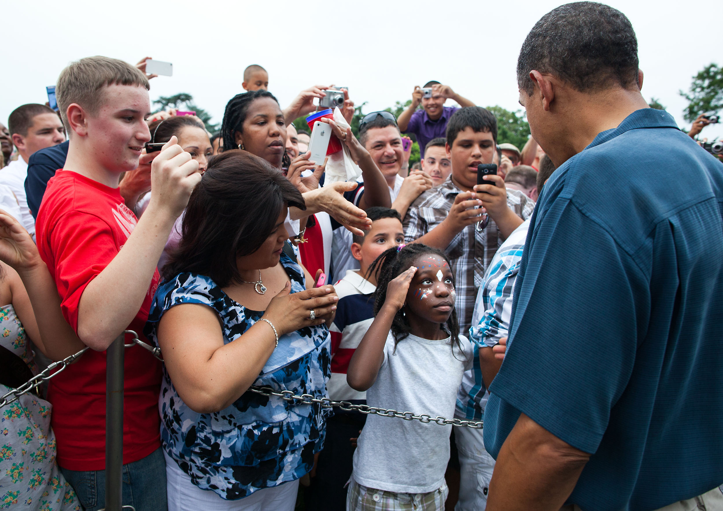 """July 4, 2011                               Pete Souza: """"I was lucky to make this frame of a young girl saluting President Obama as he shook hands along a rope line with members of the military and their families before the fireworks.""""                               President Barack Obama and First Lady Michelle Obama welcome military families attending the Fourth of July celebration on the South Lawn of the White House, July 4, 2011."""