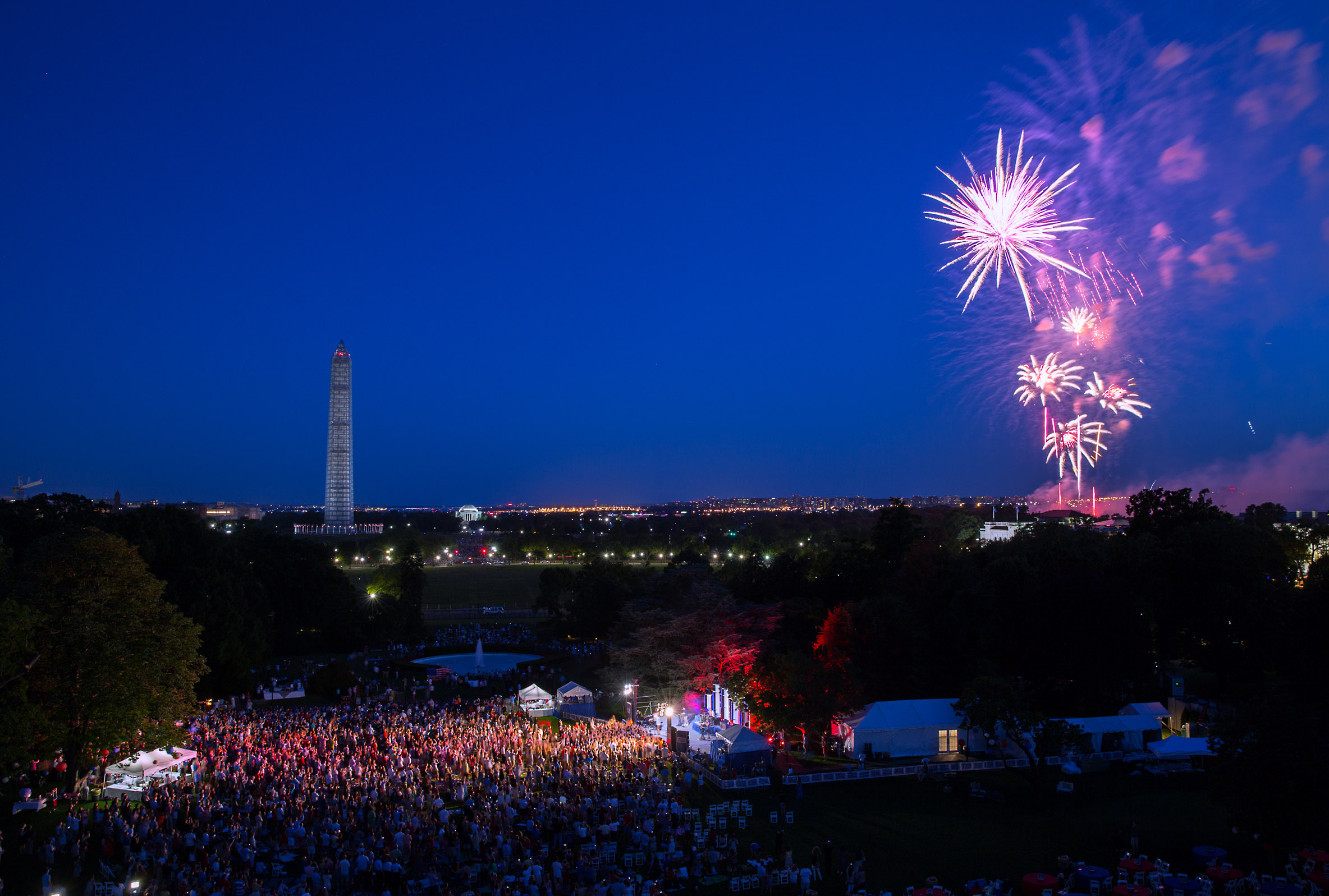 """July 4, 2013                               Pete Souza: """"Although I almost never have a tripod with me, I sometimes set up a tripod to capture the beginning of the fireworks. The band is supposed to be done with their music when the fireworks start, but this year they were still playing their last song and some of the lights from the stage were still illuminating the crowd on the South Lawn.""""President Barack Obama and First Lady Michelle Obama watch fireworks from the roof of the White House during a Fourth of July celebration for military families and White House Staff on the South Lawn, July 4, 2013."""