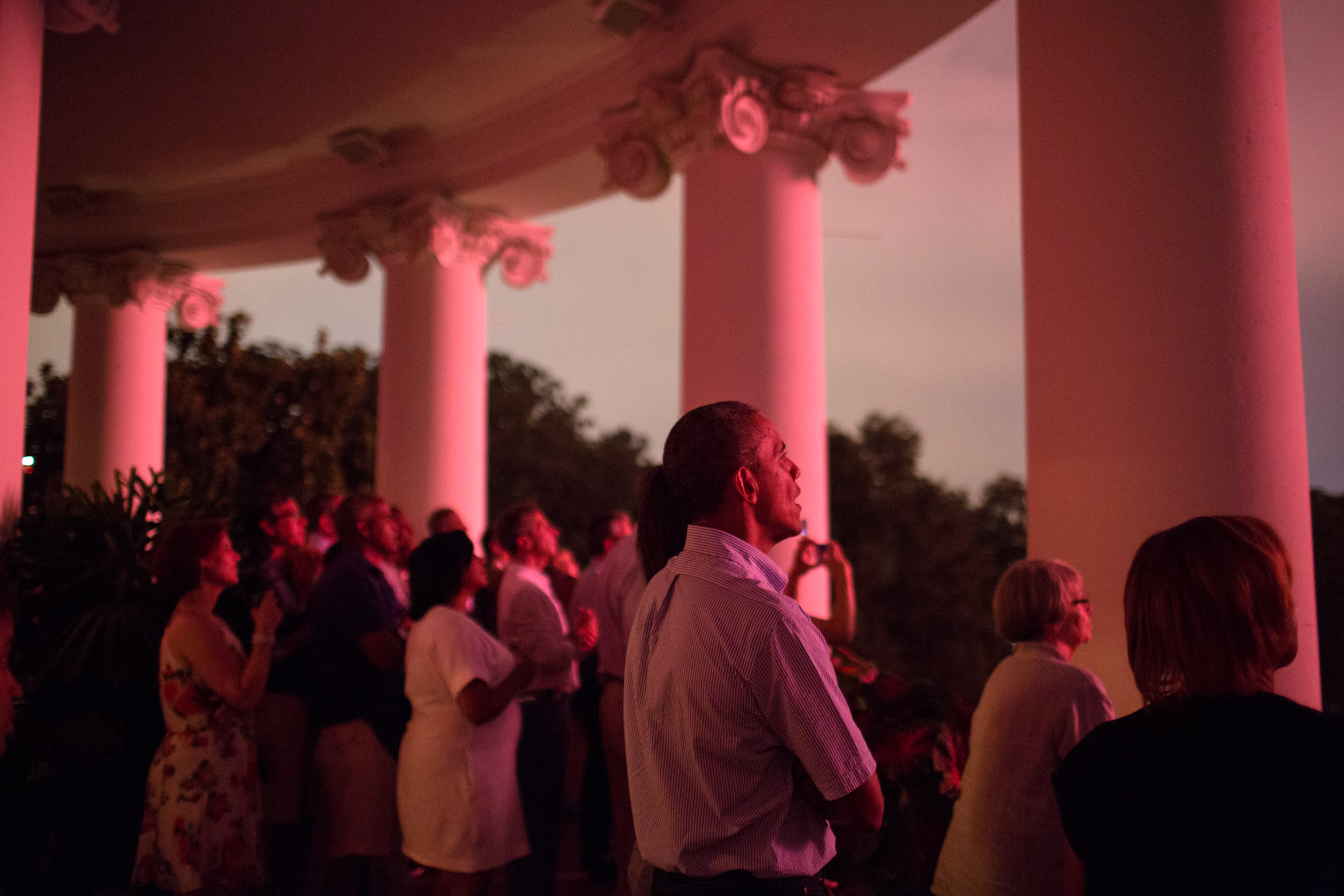 """July 4, 2015                               Pete Souza: """"Because it had rained out their family barbecue, the Obamas and their family and friends move to the Truman Balcony and watched the beginning of the fireworks from there before moving up to the roof.""""President Barack Obama, First Lady Michelle Obama, daughters Sasha and Malia, and family and friends watch the Fourth of July fireworks from the Truman Balcony of the White House, Saturday, July 4, 2015."""