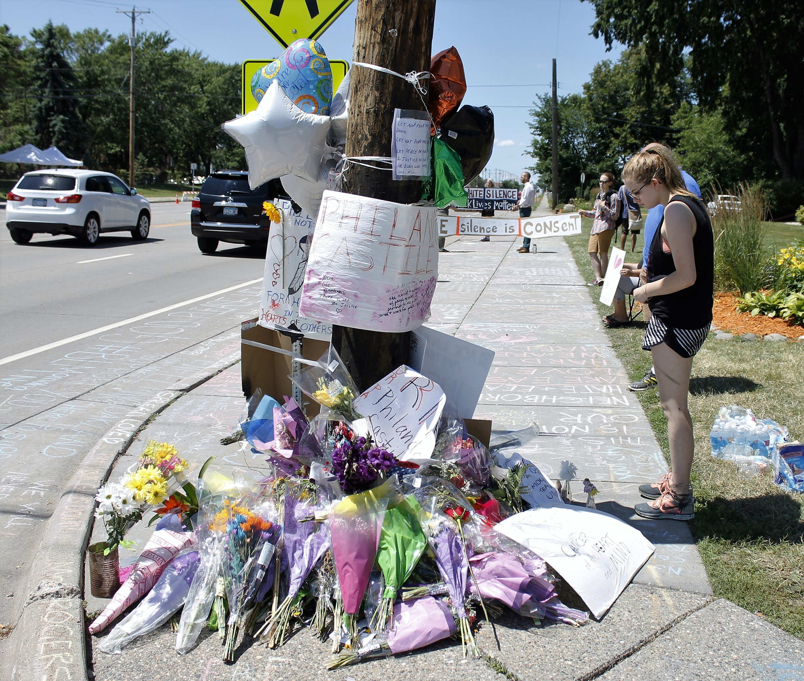 A person looks at a memorial in the Minneapolis suburb of Falcon Heights near the spot where Philando Castile was shot and killed by a police officer, July 9, 2016.