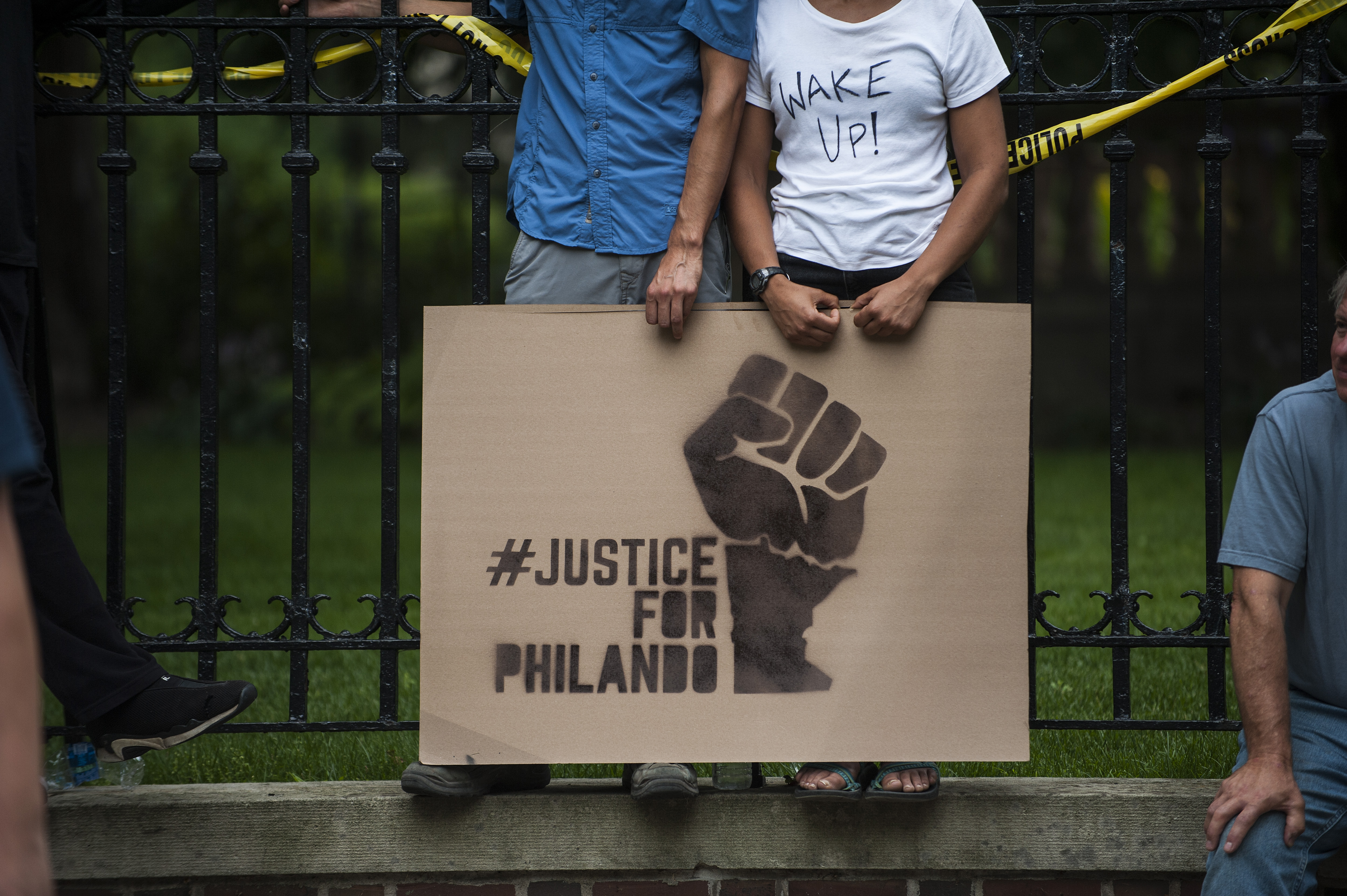 A couple hold a sign protesting the killing of Philando Castile outside the Governor's Mansion on July 7, 2016 in St. Paul, Minnesota.