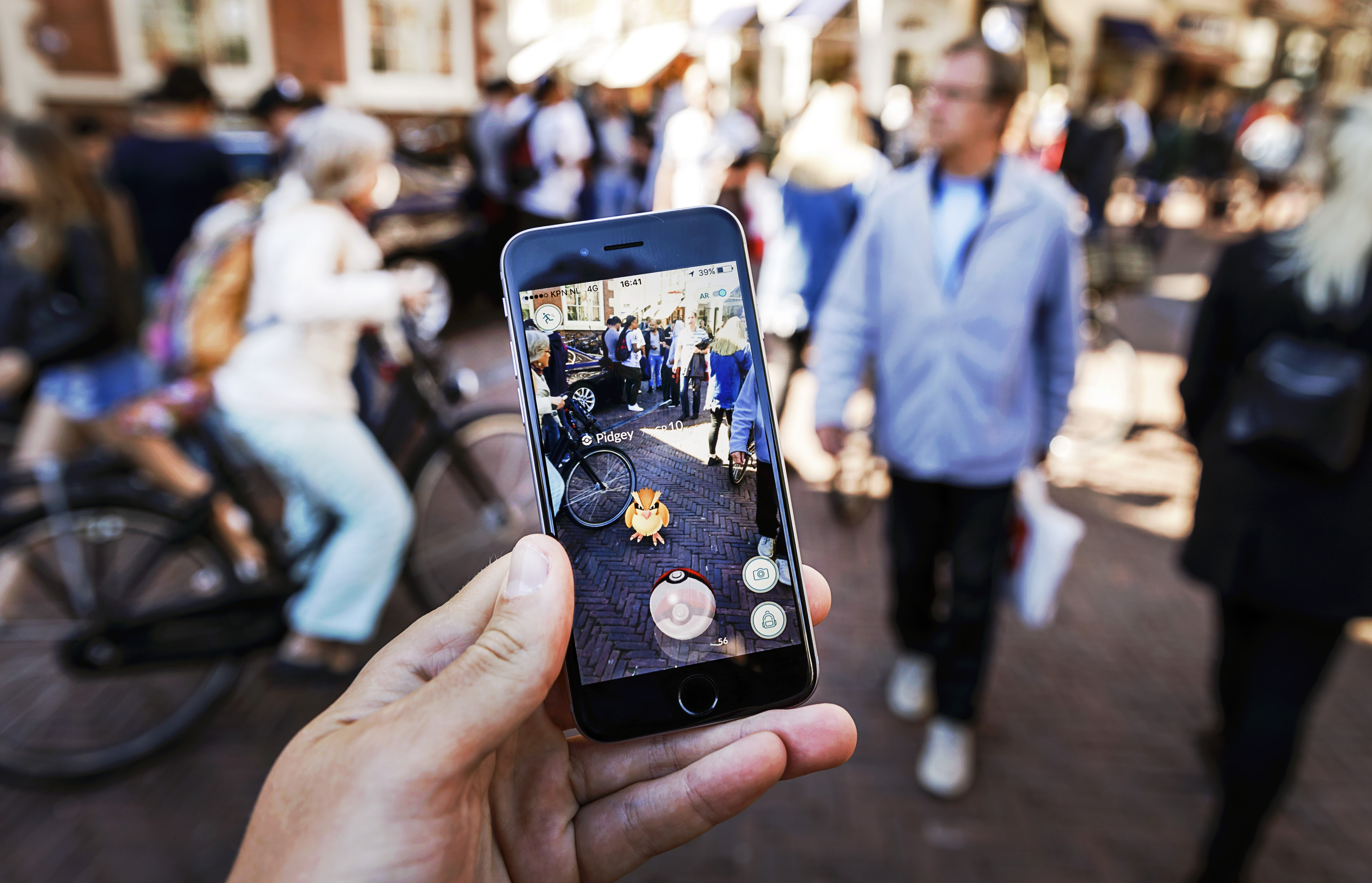 Gamers play with the Pokemon Go application on their mobile phone, at the Grote Markt in Haarlem, on July 13, 2016.