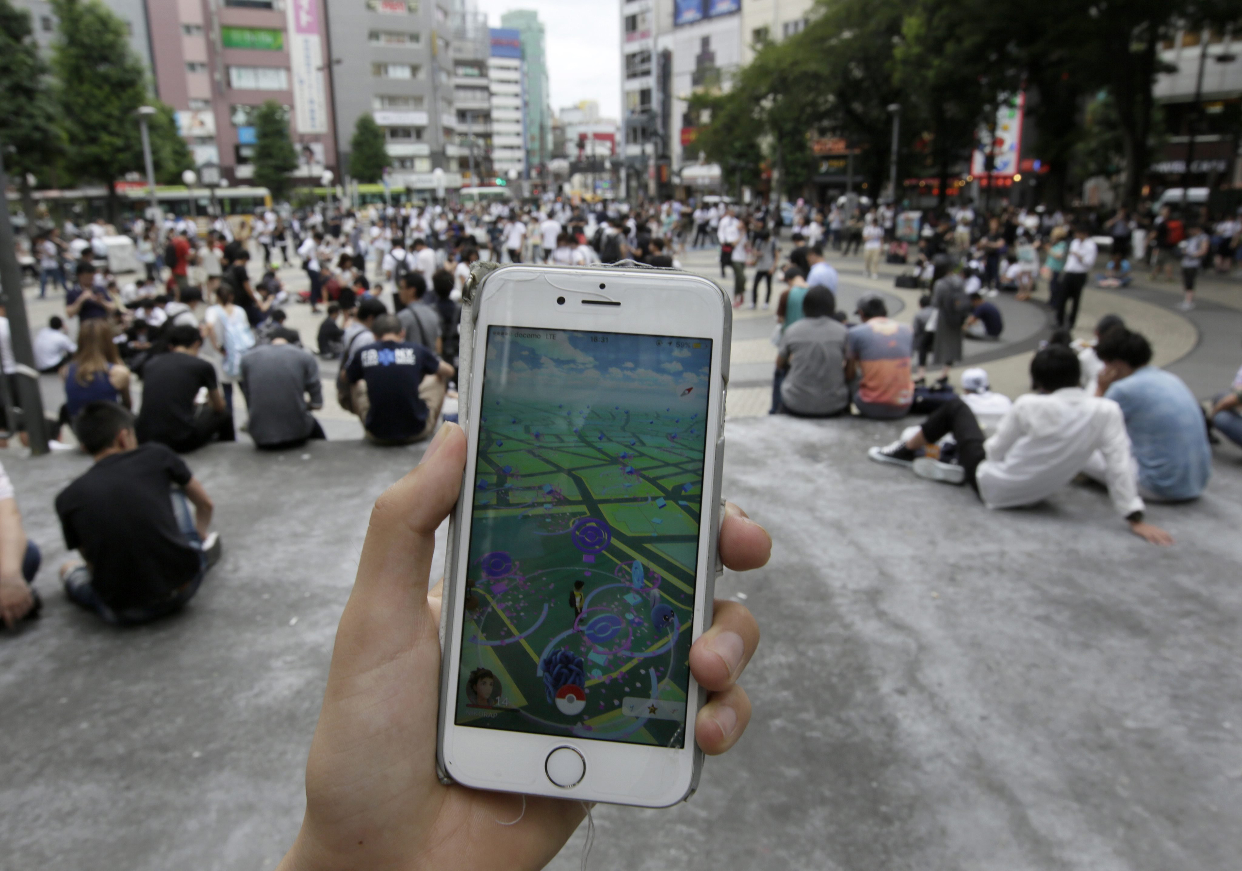 People play Pokemon Go at a park in Tokyo on July 25, 2016.