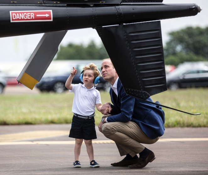 Britain's Prince George points as he and his father, Prince William, look at a 'Squirrel' helicopter during a visit to the Royal International Air Tattoo at RAF Fairford in western England on July 8, 2016.