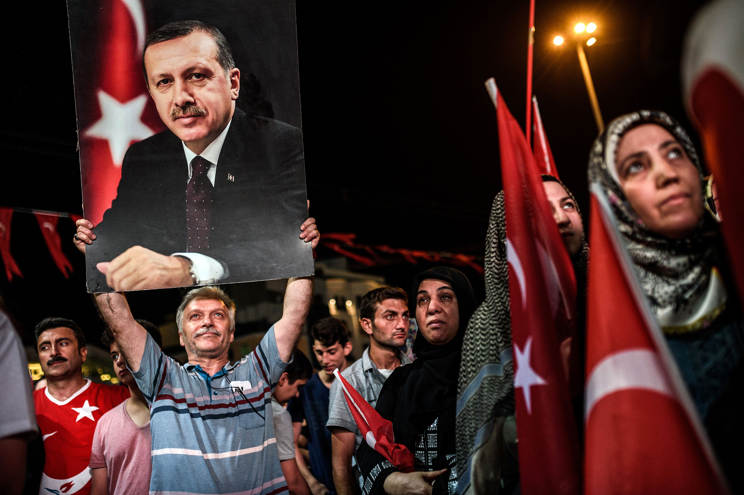 A man holds up a photo of Turkey's President Recep Tayyip Erdogan during a pro-Erdogan rally in Taksim Square in Istanbul on July 22, 2016.