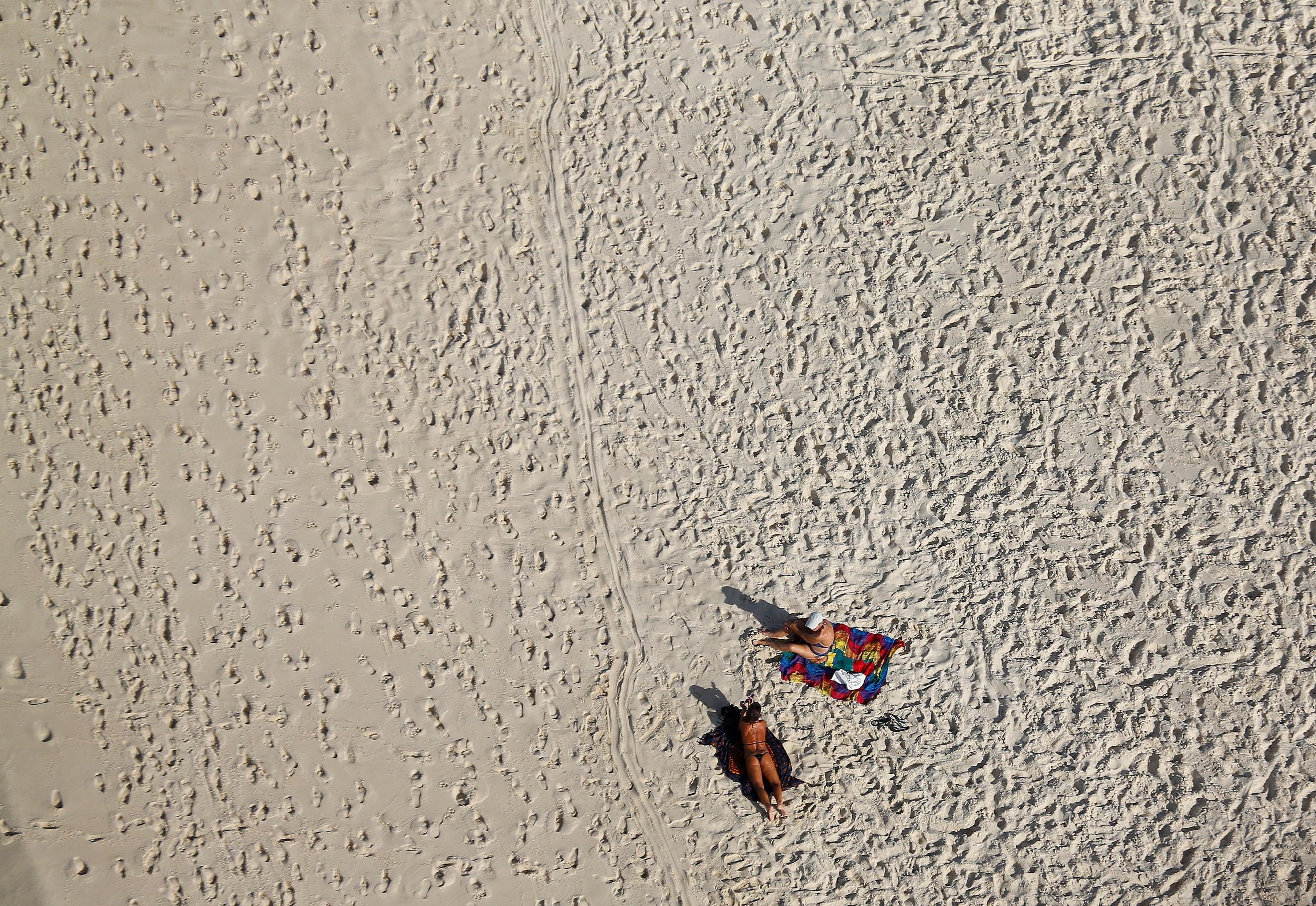 An aerial view shows people on Barra da Tijuca beach in Rio de Janeiro on July 16, 2016.
