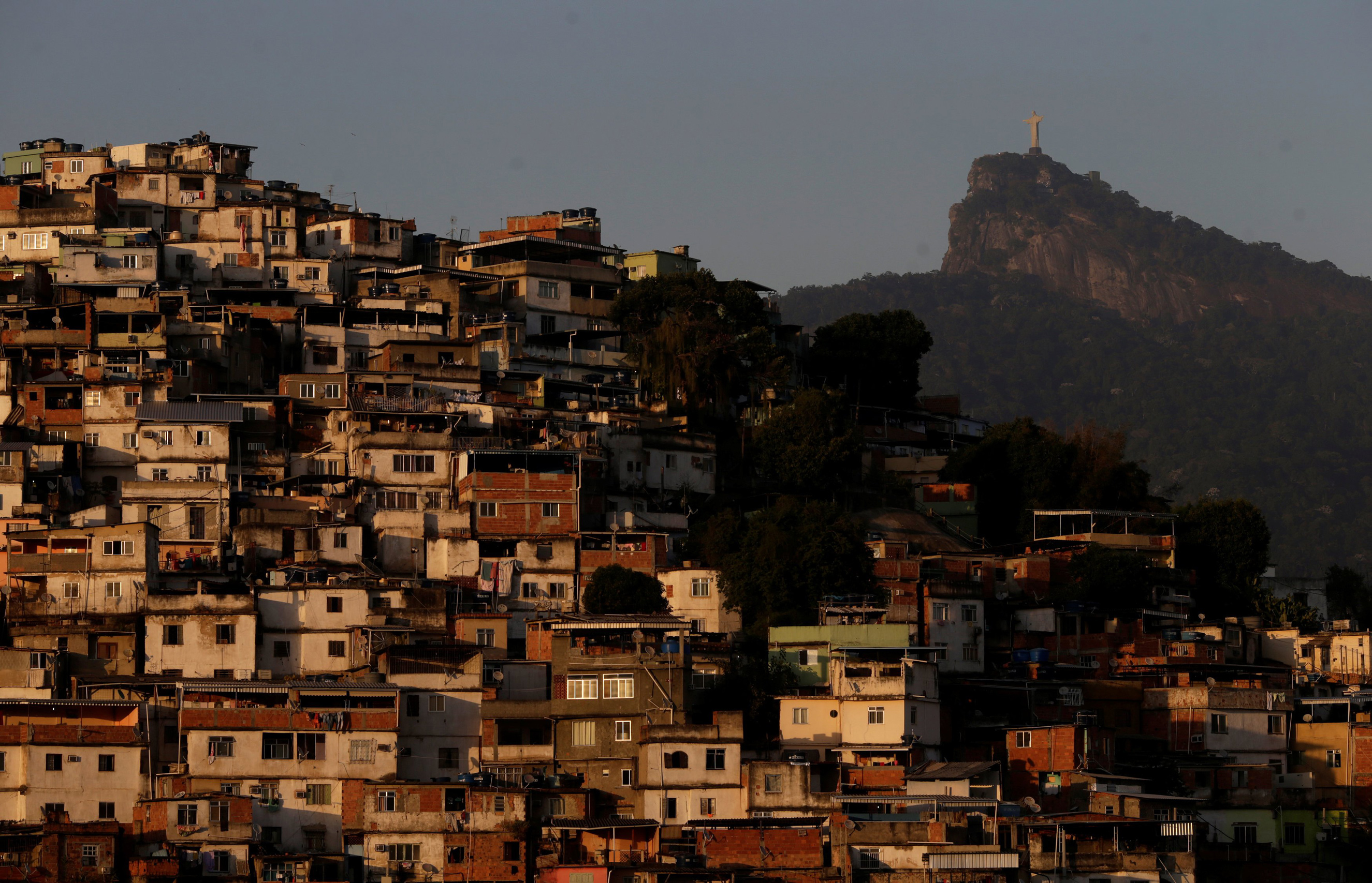 Christ the Redeemer is seen behind Morro da Coroa (Coroa slum) in Rio de Janeiro on July 13, 2016.