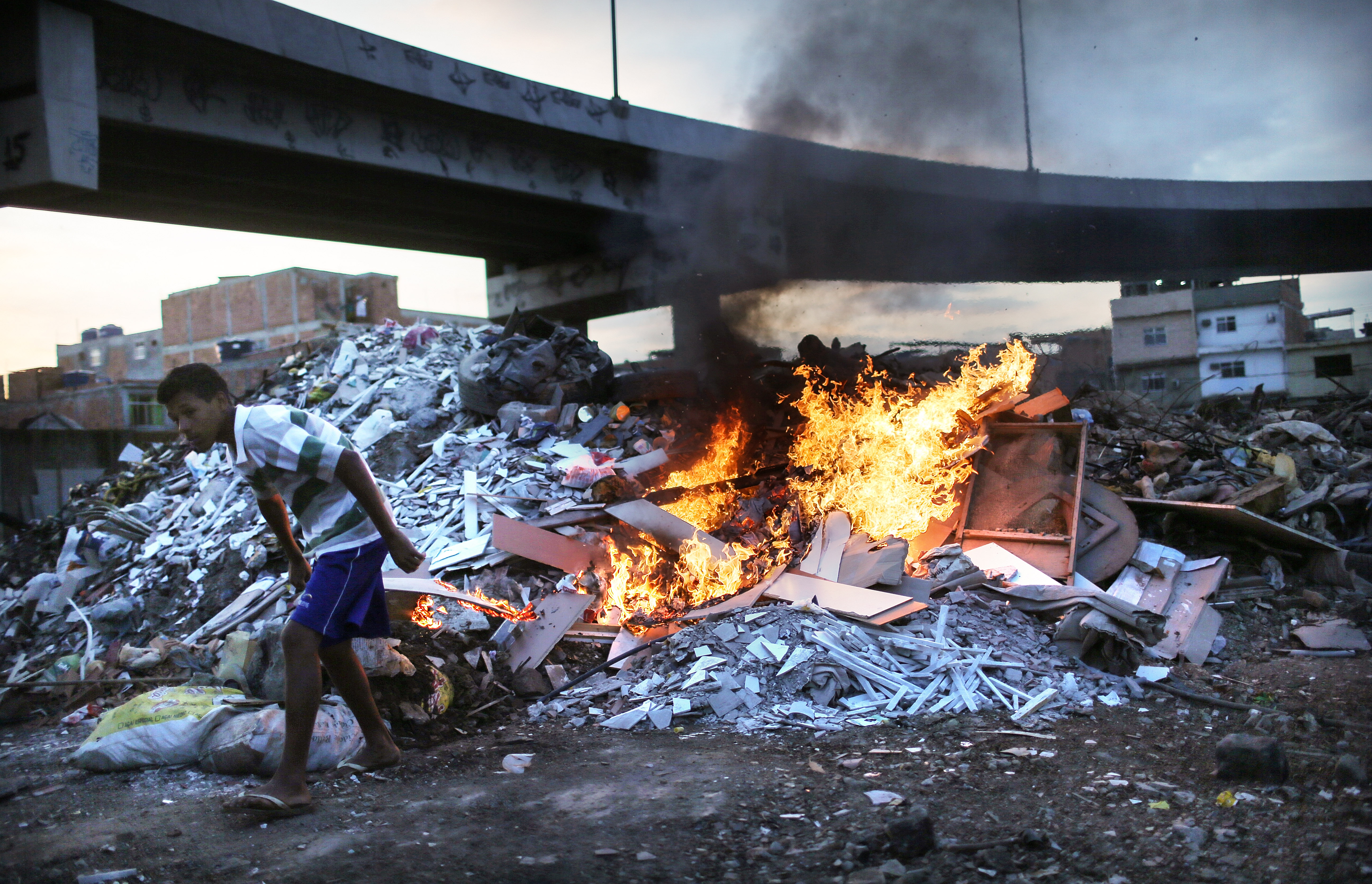 Trash is burned in an area where garbage is dumped near the main highway linking Rio's international airport to the city in the Mare favela community complex in Rio de Janeiro on July 18, 2016.