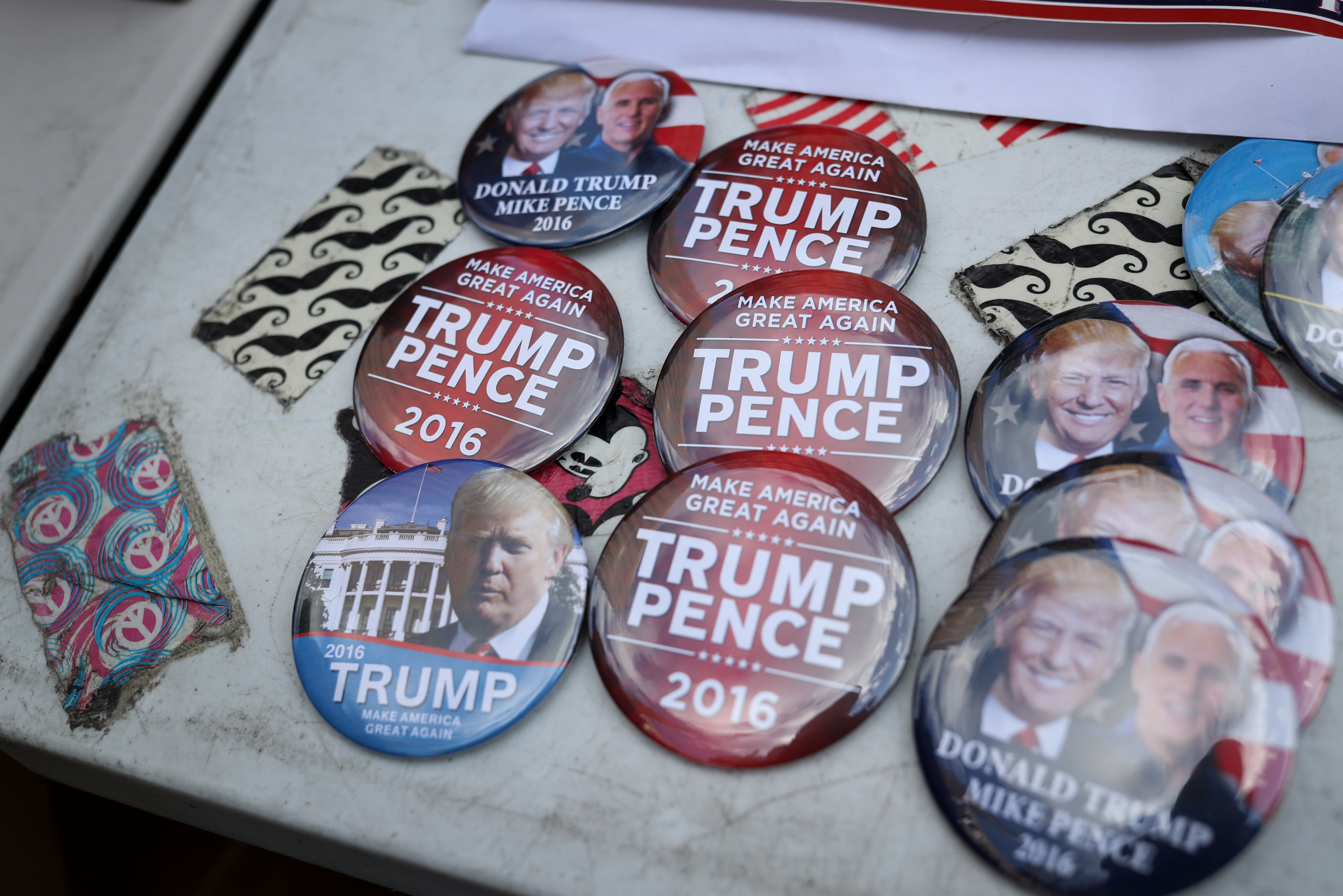 Buttons in support of Donald Trump, presumptive 2016 Republican presidential nominee, and Mike Pence, presumptive 2016 Republican vice presidential nominee, are displayed ahead of the Republican National Convention (RNC) in Cleveland, Ohio, U.S., on July 17, 2016.
