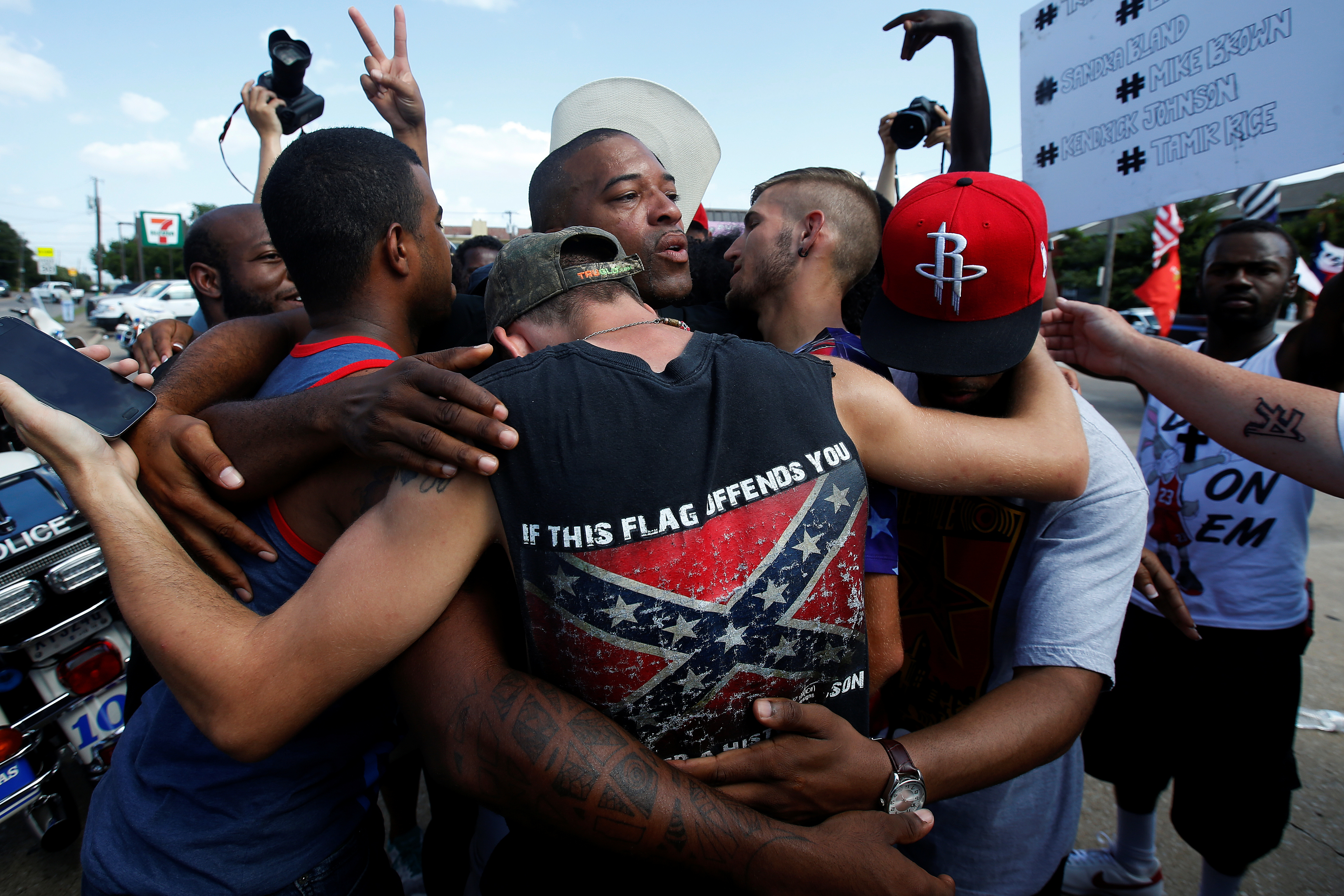 People, including a man wearing a T-shirt with a Confederate flag, hug in Dallas on July 10, 2016, following a Black Lives Matter rally protesting the multiple police shootings