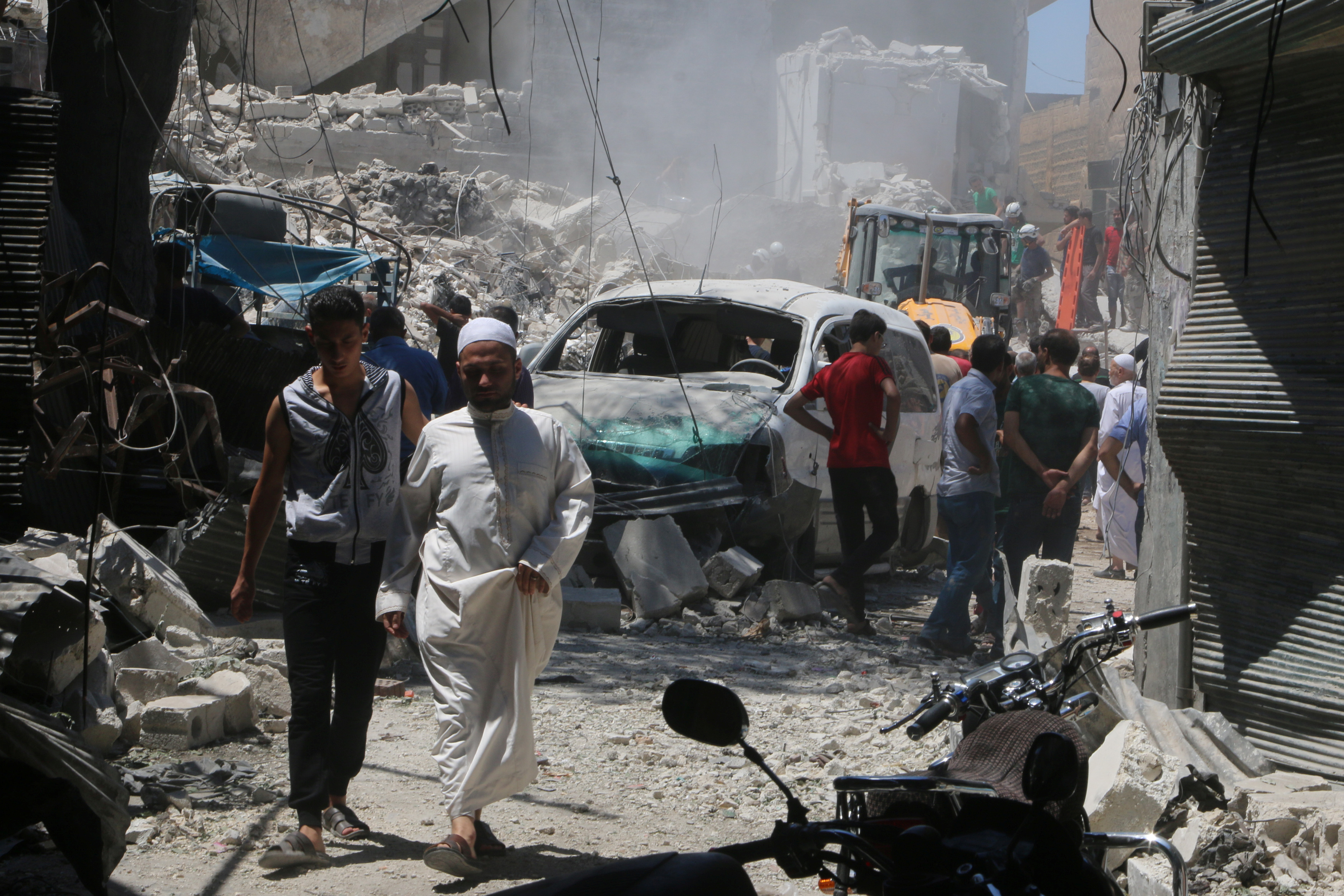 People inspect the damage at a site hit by a barrel bomb in the rebel held area of Old Aleppo, Syria on July 11, 2016