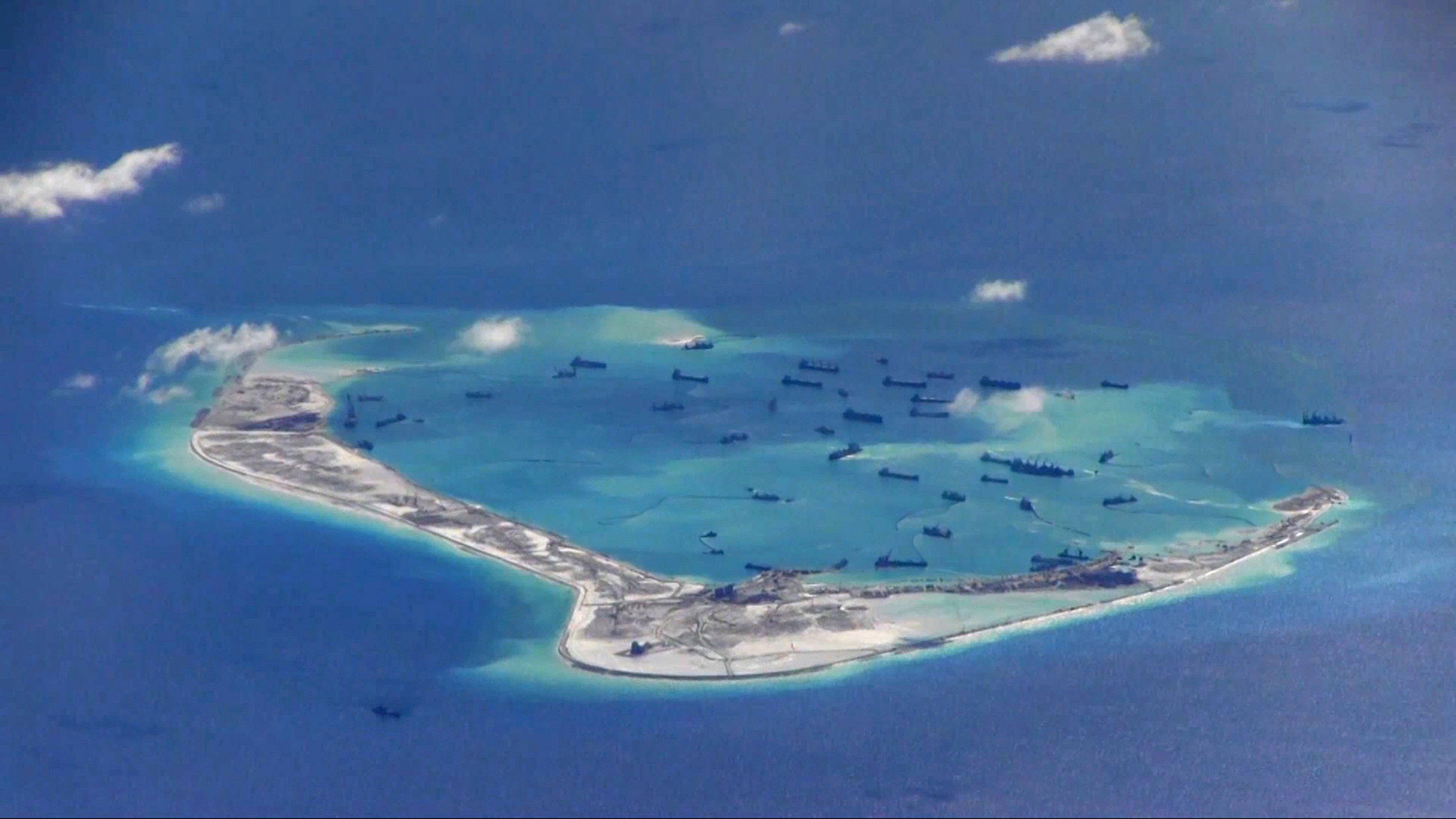 Chinese dredging vessels purportedly in the waters around Mischief Reef in the disputed Spratly Islands in the South China Sea in this still video image from a P-8A Poseidon surveillance aircraft provided by the U.S. Navy on May 21, 2015
