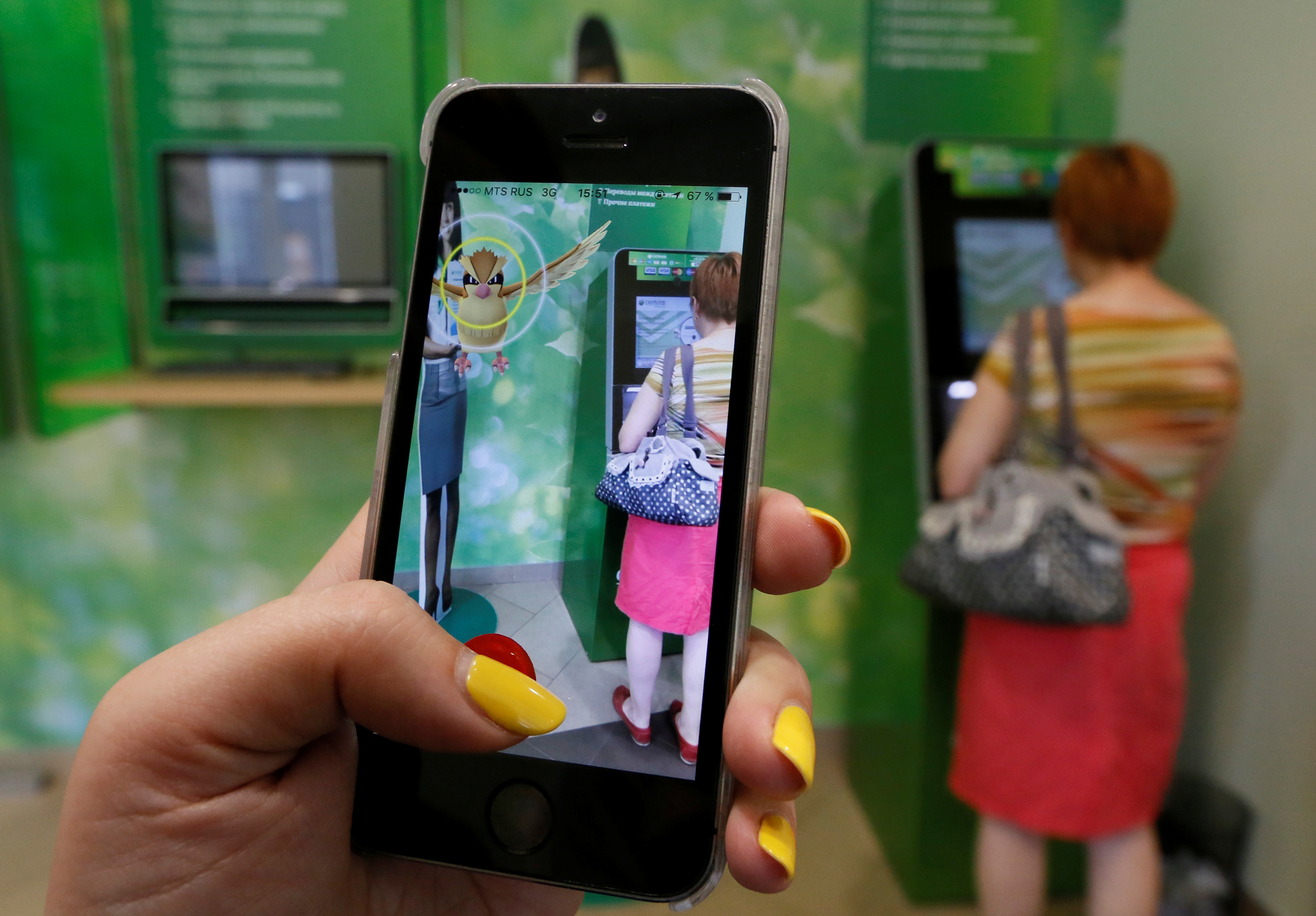 A woman plays the augmented reality mobile game  Pokemon Go  by Nintendo, as a visitor uses an (ATM) at a branch of Sberbank in central Krasnoyarsk, Siberia, Russia, July 20, 2016.