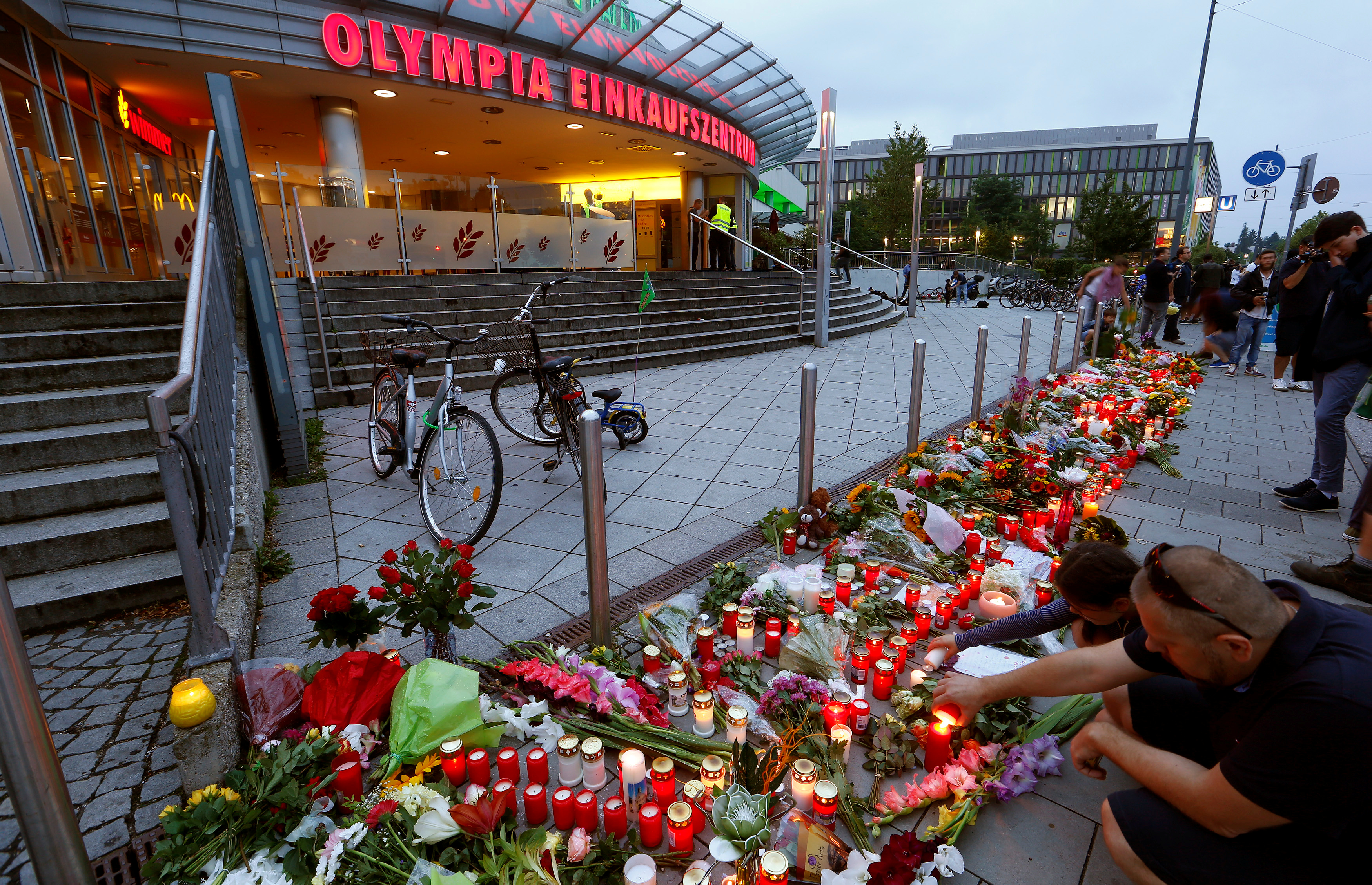 People light candles beside flowers laid in front of the Olympia shopping mall where a shooting rampage started in Munich on July 23, 2016.