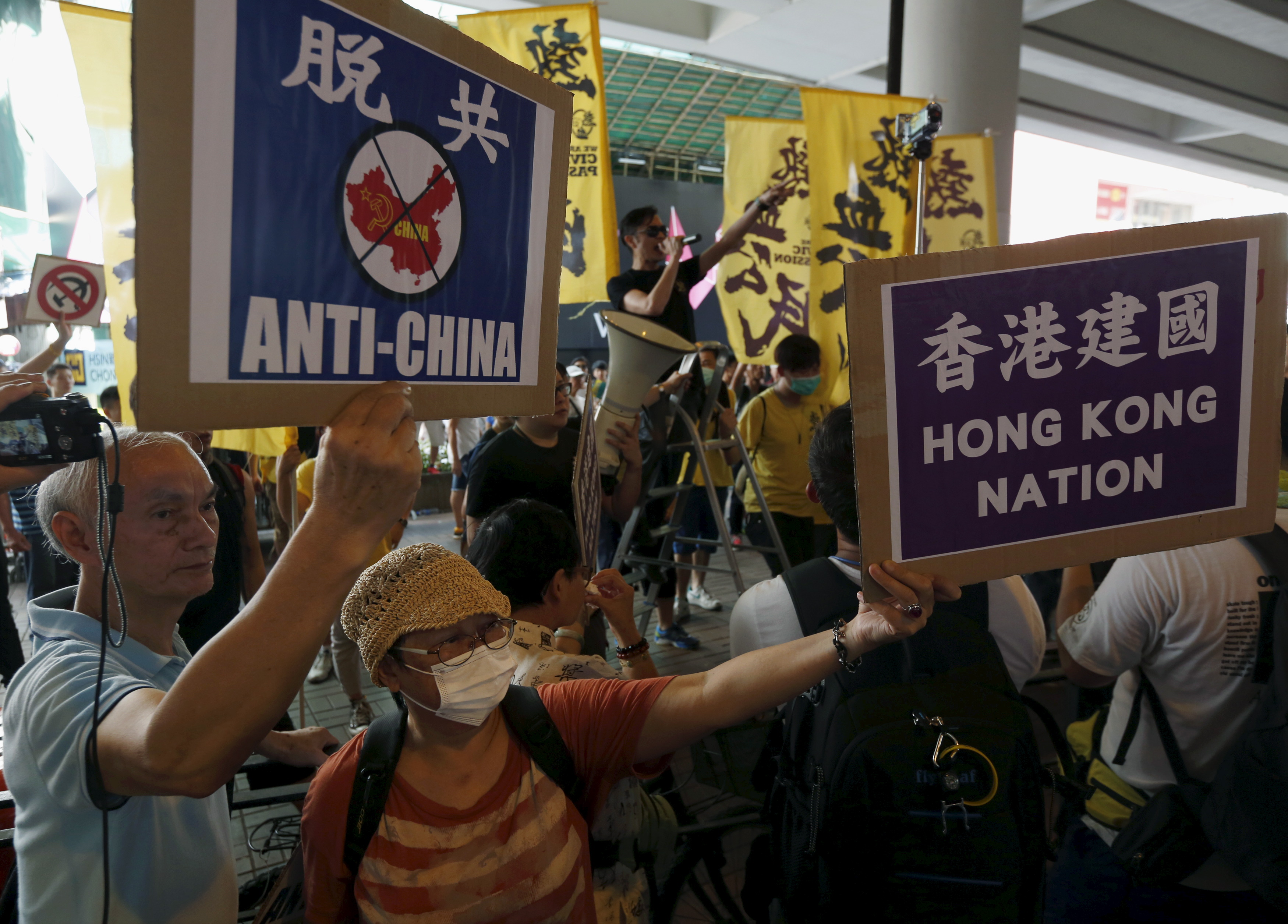 Protesters hold up placards as others shout against pro-China supporters (not in picture) during a demonstration in Hong Kong on July 1, 2015
