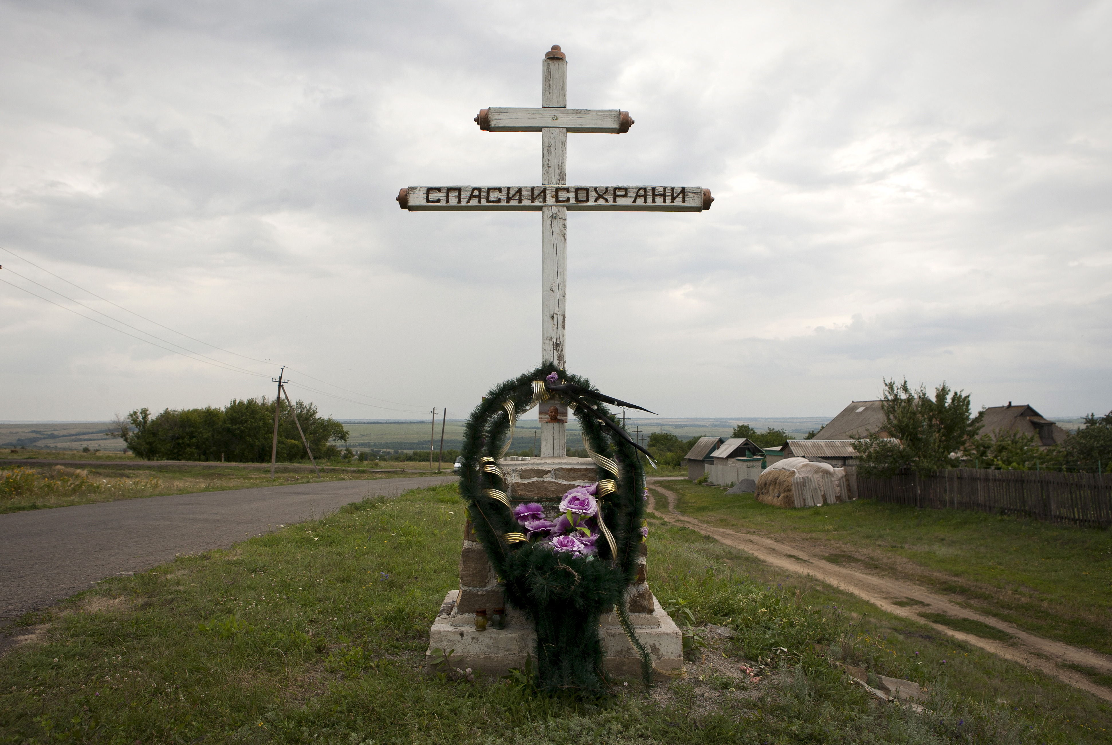 A wreath is placed on a cross with an inscription that reads  Save and protect  next to the site of the downed Malaysia Airlines flight MH17, near the village of Hrabove (Grabovo) in Donetsk region, eastern Ukraine, July 14, 2015.