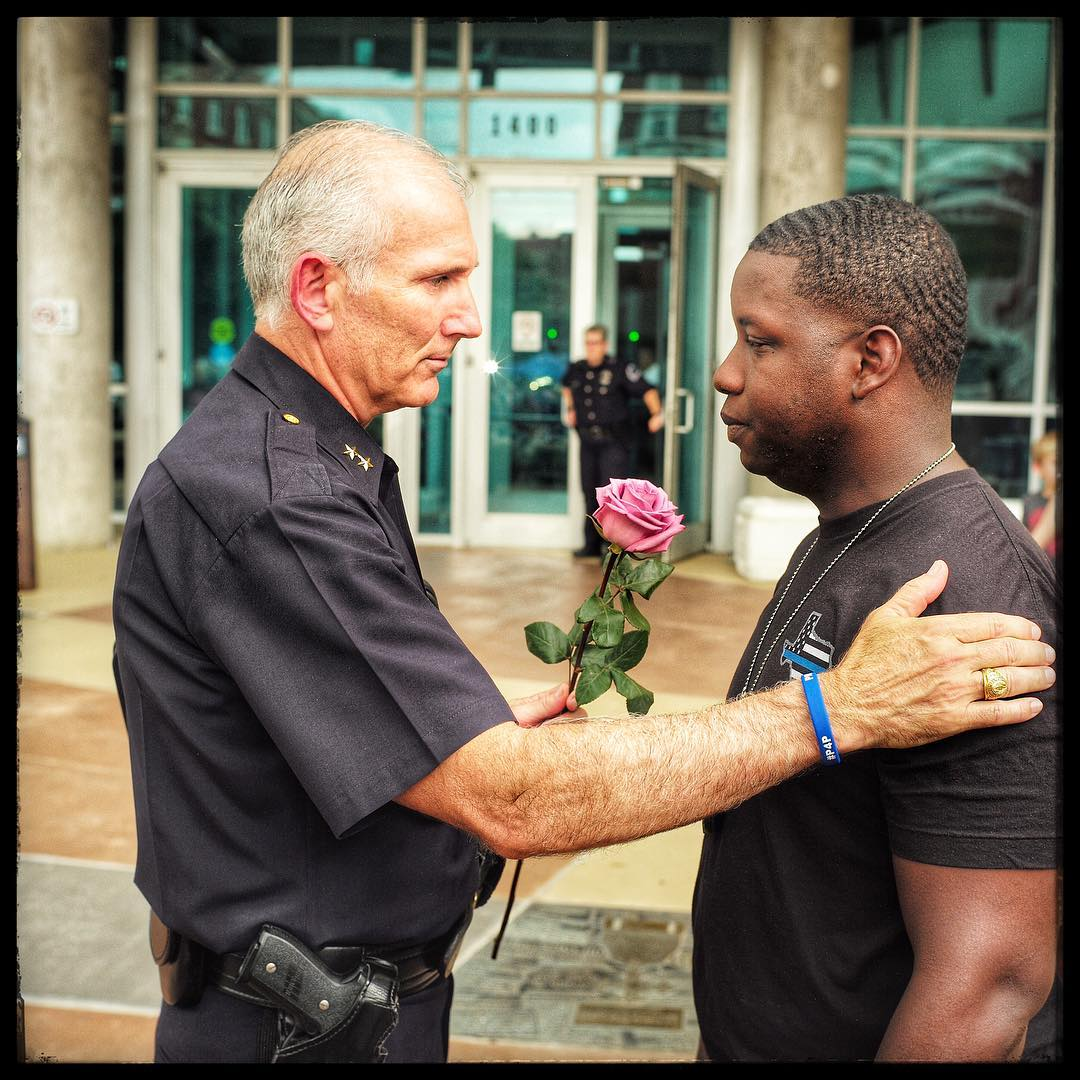 Assistant Chief of Police Gary Tittle comforts a young man in front of the police station where a memorial was erected for people to come and grieve. Dallas, Texas.