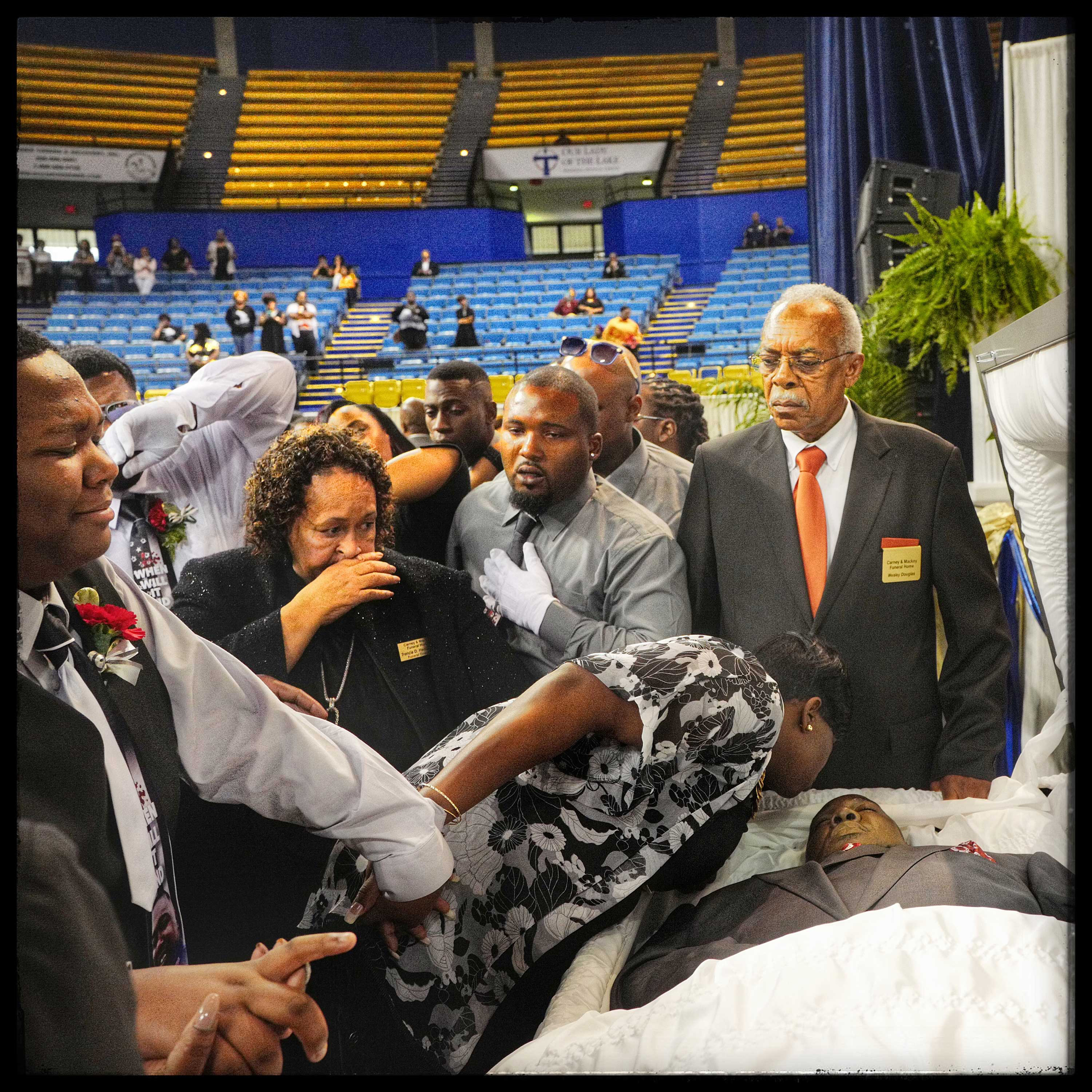 Baton Rouge, La.: Quinyetta McMillon says her final goodbye to Alton Sterling with a kiss as their 15-year-old son Cameron looks on with tears. They are flanked by relatives who rushed to the front to say goodbye for the final time.
