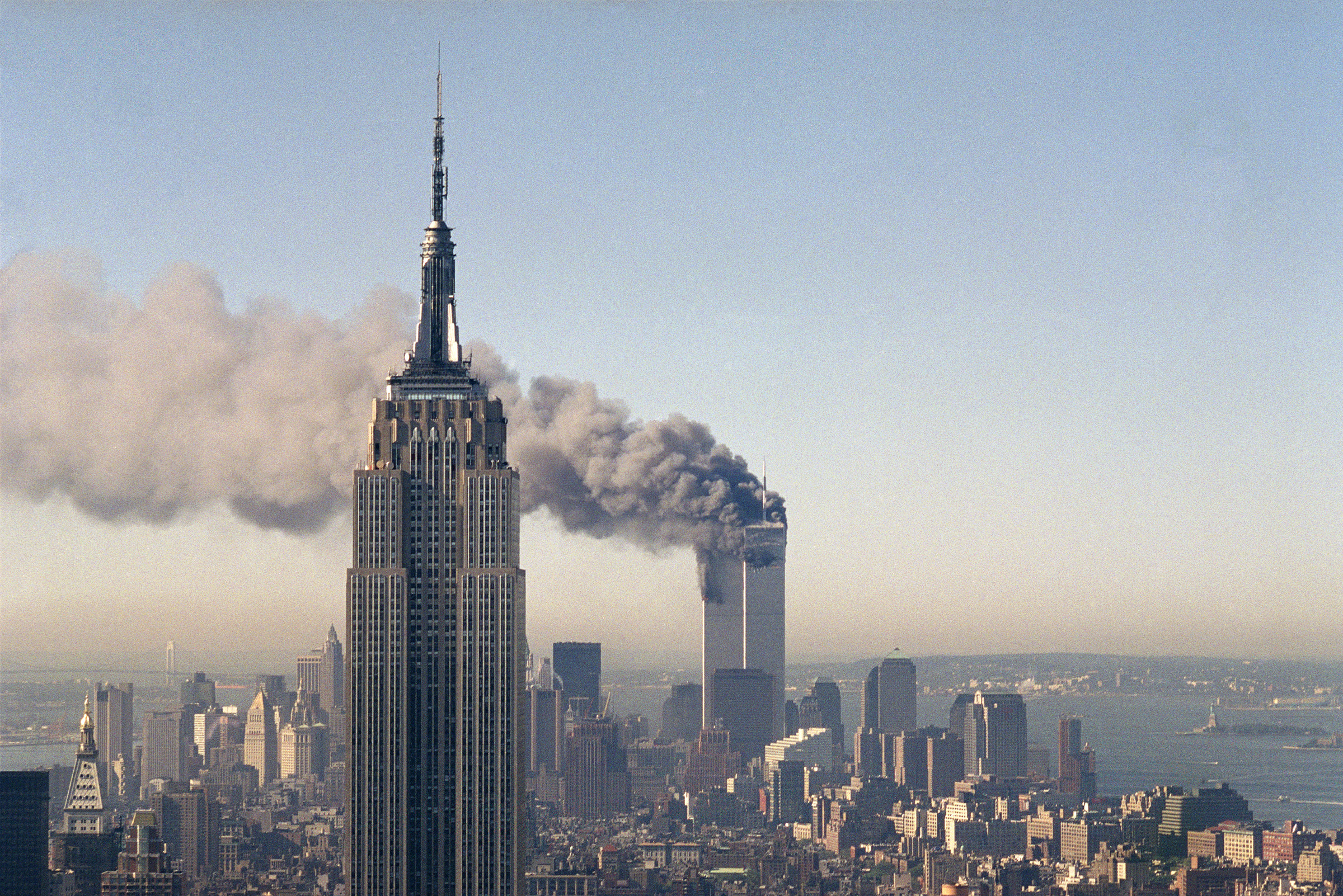 The twin towers of the World Trade Center burn behind the Empire State Building in New York after terrorists crashed two planes into the towers causing both to collapse, Sept. 11, 2001.