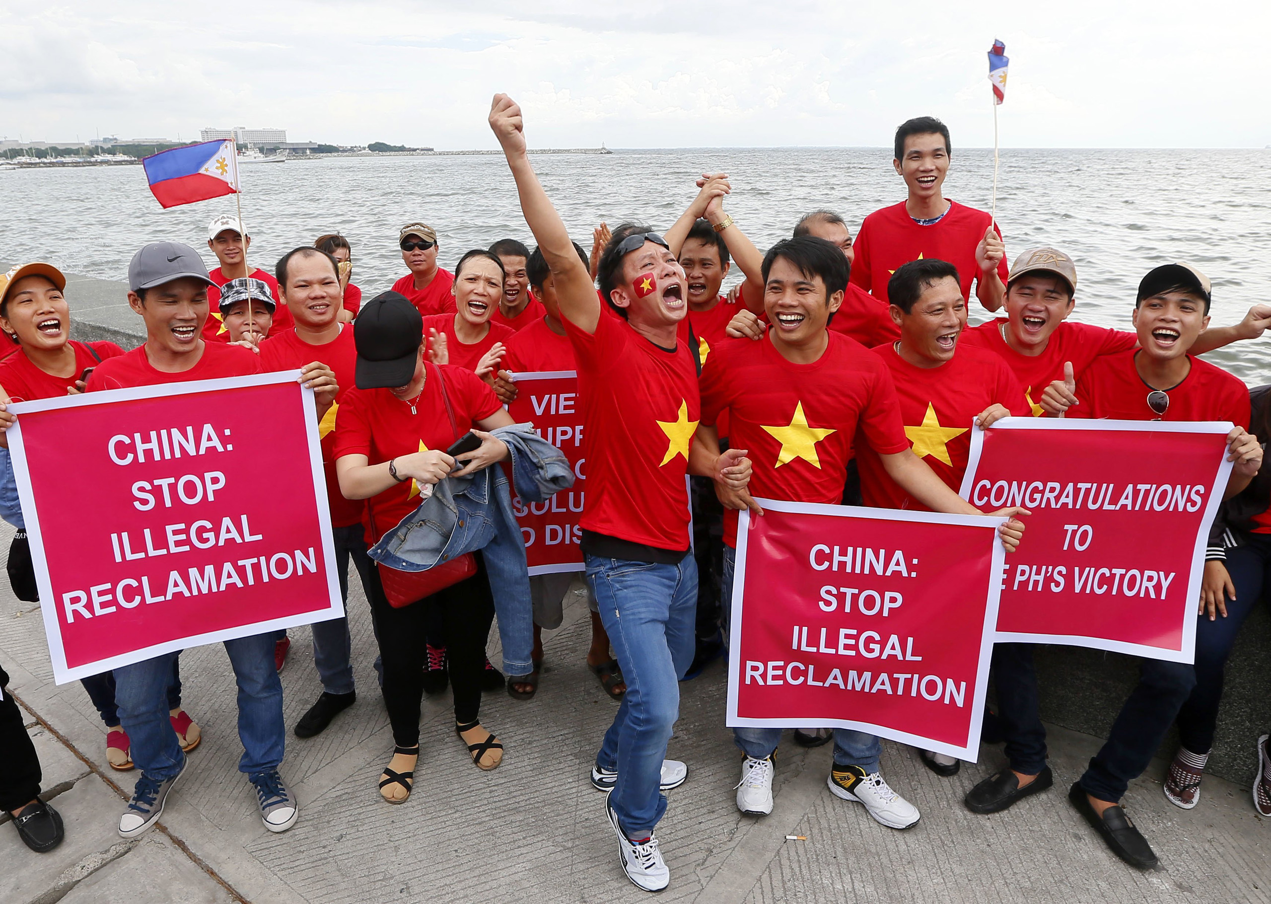 Vietnamese expatriates cheer while displaying placards during a rally by the Manila's baywalk before the Hague-based U.N. international arbitration tribunal is to announce its ruling on South China Sea in the Philippines on July 12, 2016.