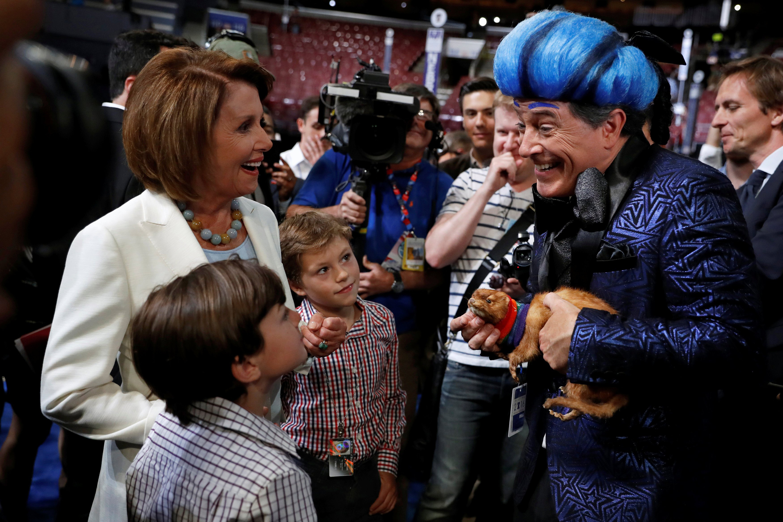 U.S. House Minority Leader Nancy Pelosi (D-CA) and two of her grandsons greet comedian Stephen Colbert (R) on the floor ahead of the 2016 Democratic National Convention in Philadelphia on July 24, 2016.